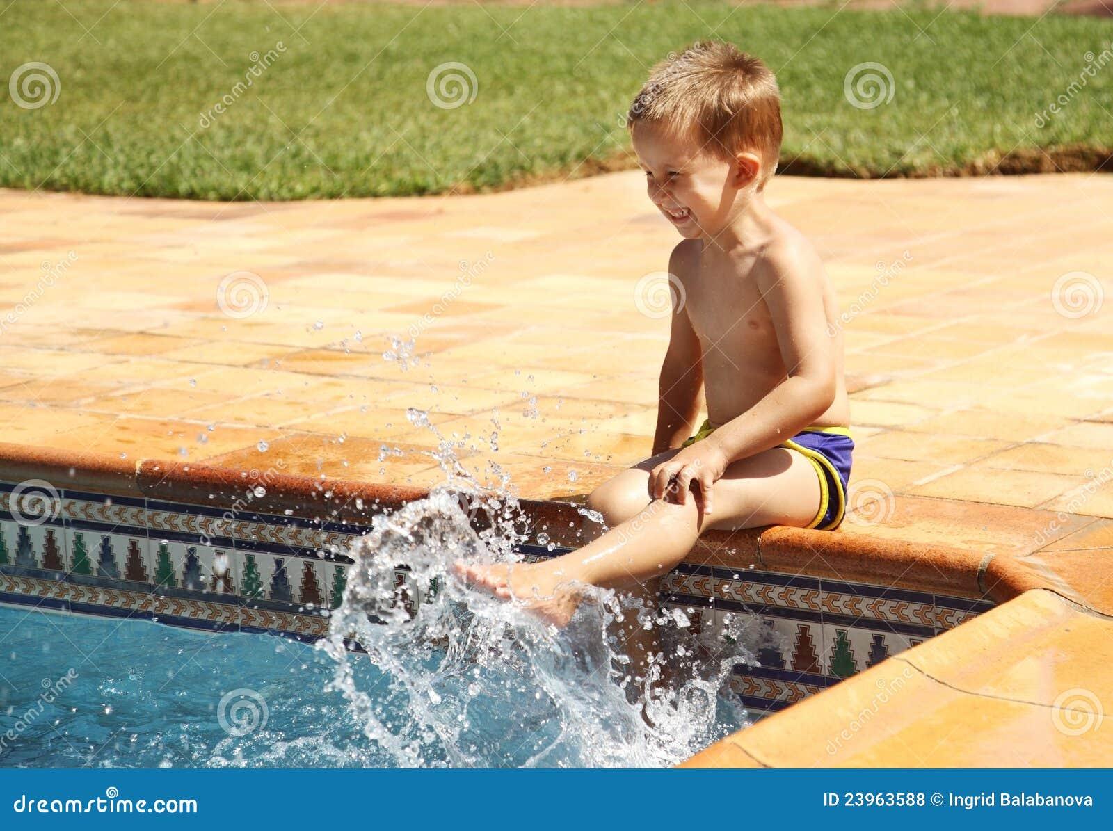 Glücklicher Junge, der Spaß am Swimmingpool hat