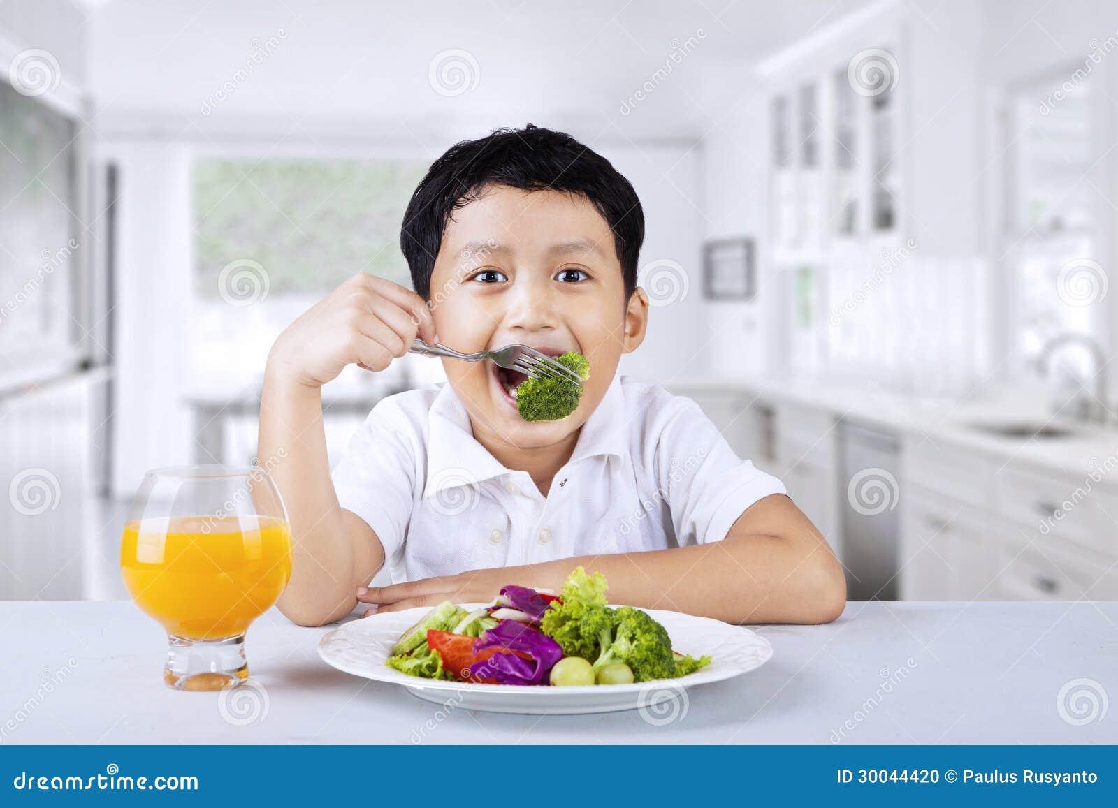 Junge, der zu Hause Brokkoli isst