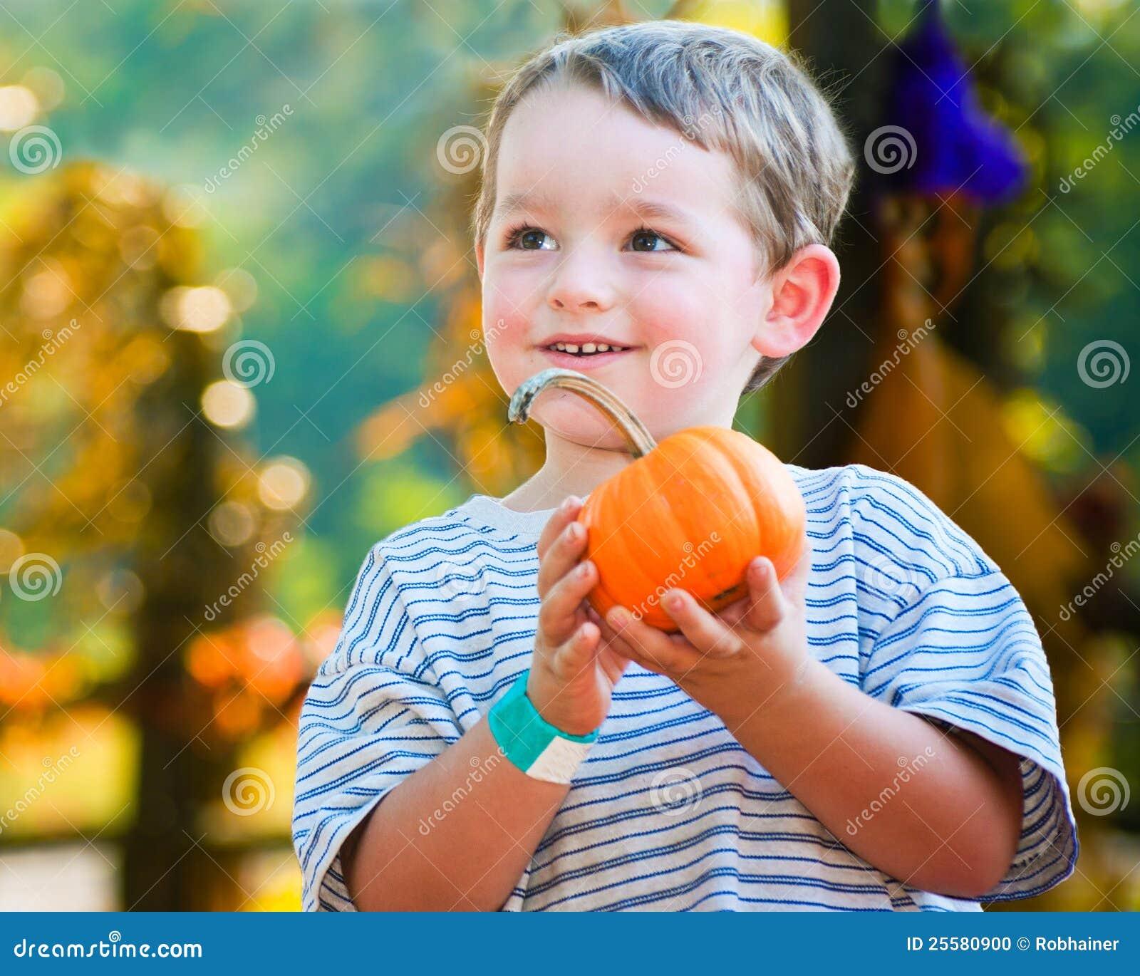 Glücklicher junger Junge, der einen Kürbis auswählt
