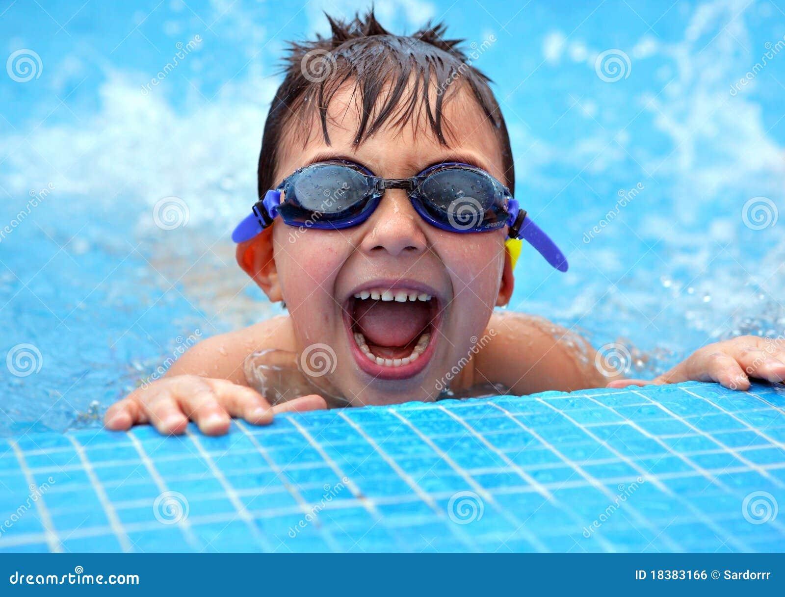Glücklicher junger lächelnder Junge im Swimmingpool