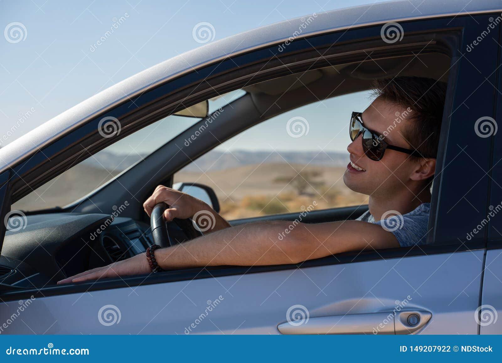 Gl?cklicher junger Mann, der ein gemietetes Auto in der W?ste von Israel f?hrt