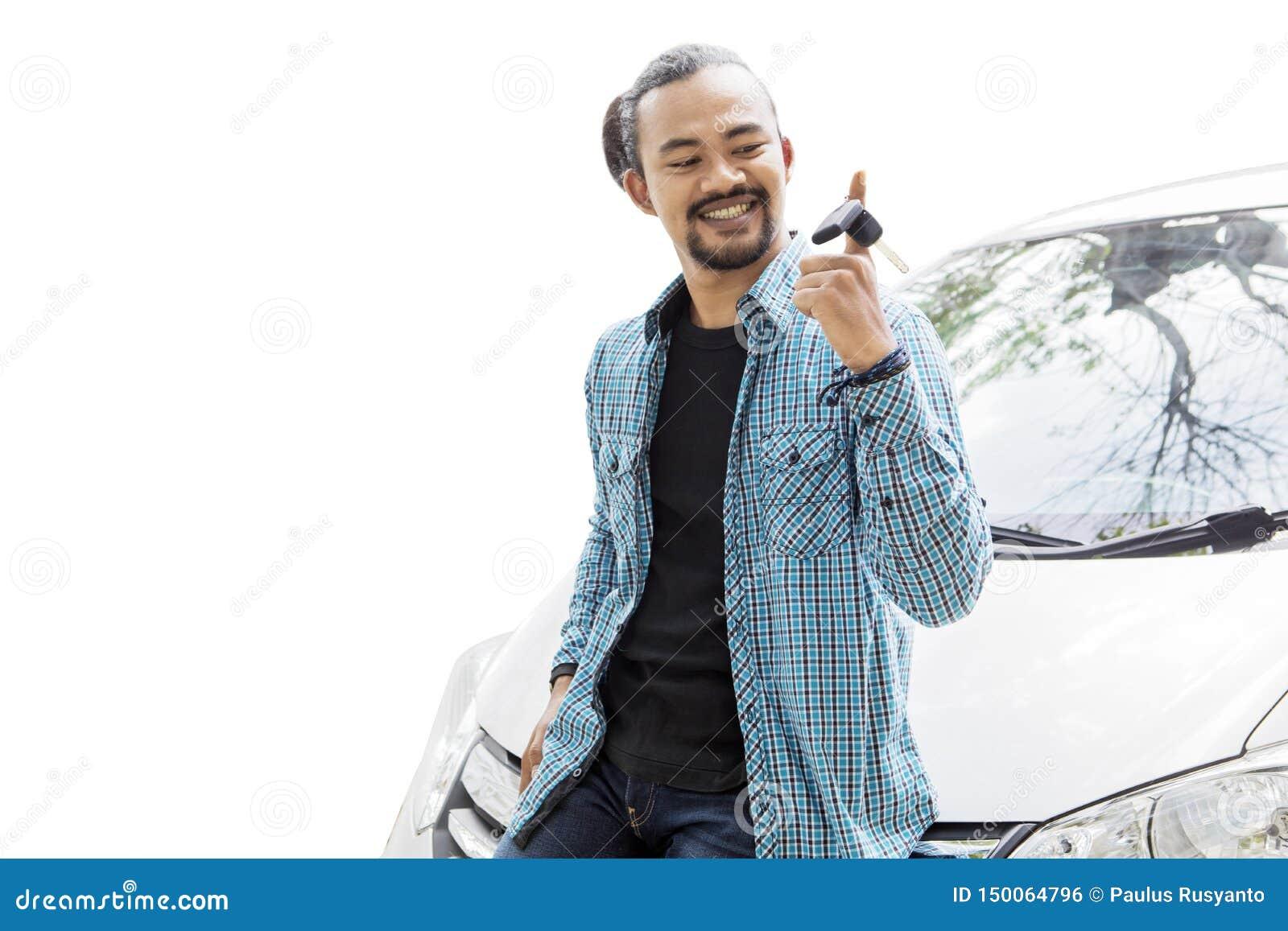 Glücklicher junger Mann, der einen Neuwagenschlüssel auf Studio verdreht