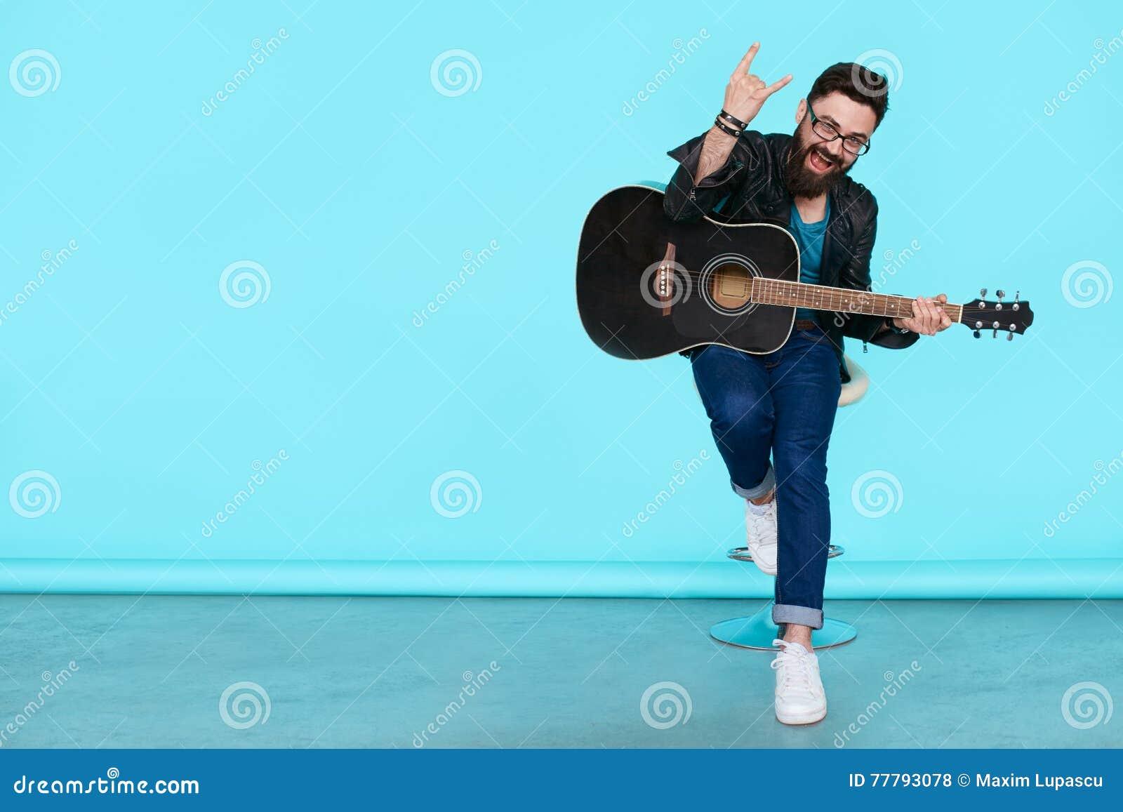 Glücklicher junger Punkrocker mit einer Gitarre und einer dunklen Sonnenbrille