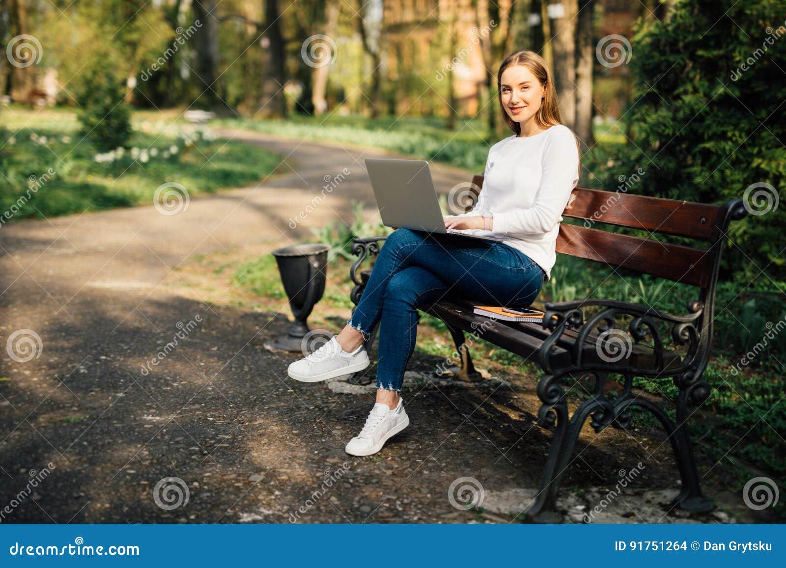 Glücklicher junger Student mit einer Tablette und einer Wegwerfkaffeetasse, die auf der Bank sitzen und in einem Sommerpark lesen