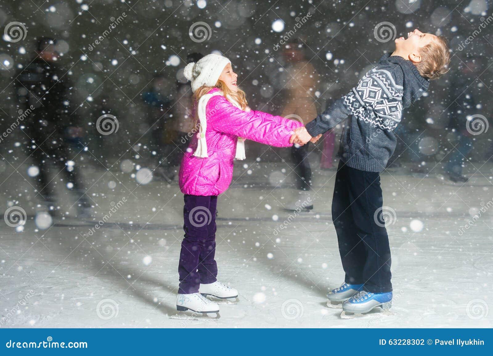 Glücklicher Kindereislauf an der Eisbahn, Winternacht