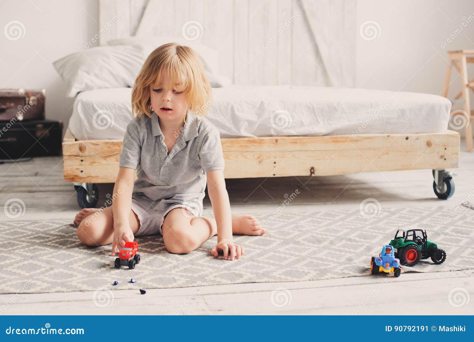 Glücklicher Kinderjunge, der zu Hause mit Spielzeugautos morgens spielt