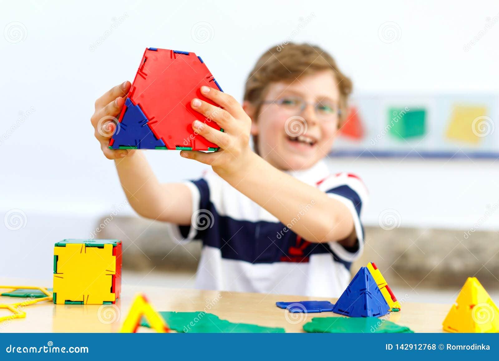 Glücklicher Kinderjunge mit den Gläsern, die Spaß mit Gebäude haben und geometrische Zahlen, Mathematik und Geometrie lernend sch