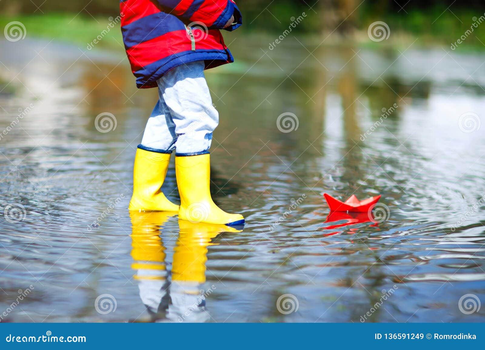 Glücklicher Kleinkindjunge in den gelben Regenstiefeln, die mit Papierschiffsboot durch enorme Pfütze am Frühlings- oder Herbstta