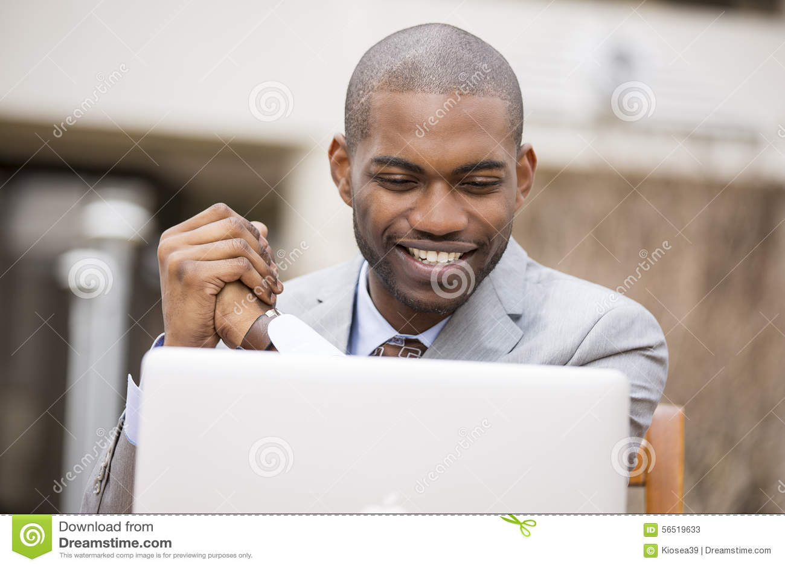 Glücklicher lächelnder Geschäftsmann mit Laptop