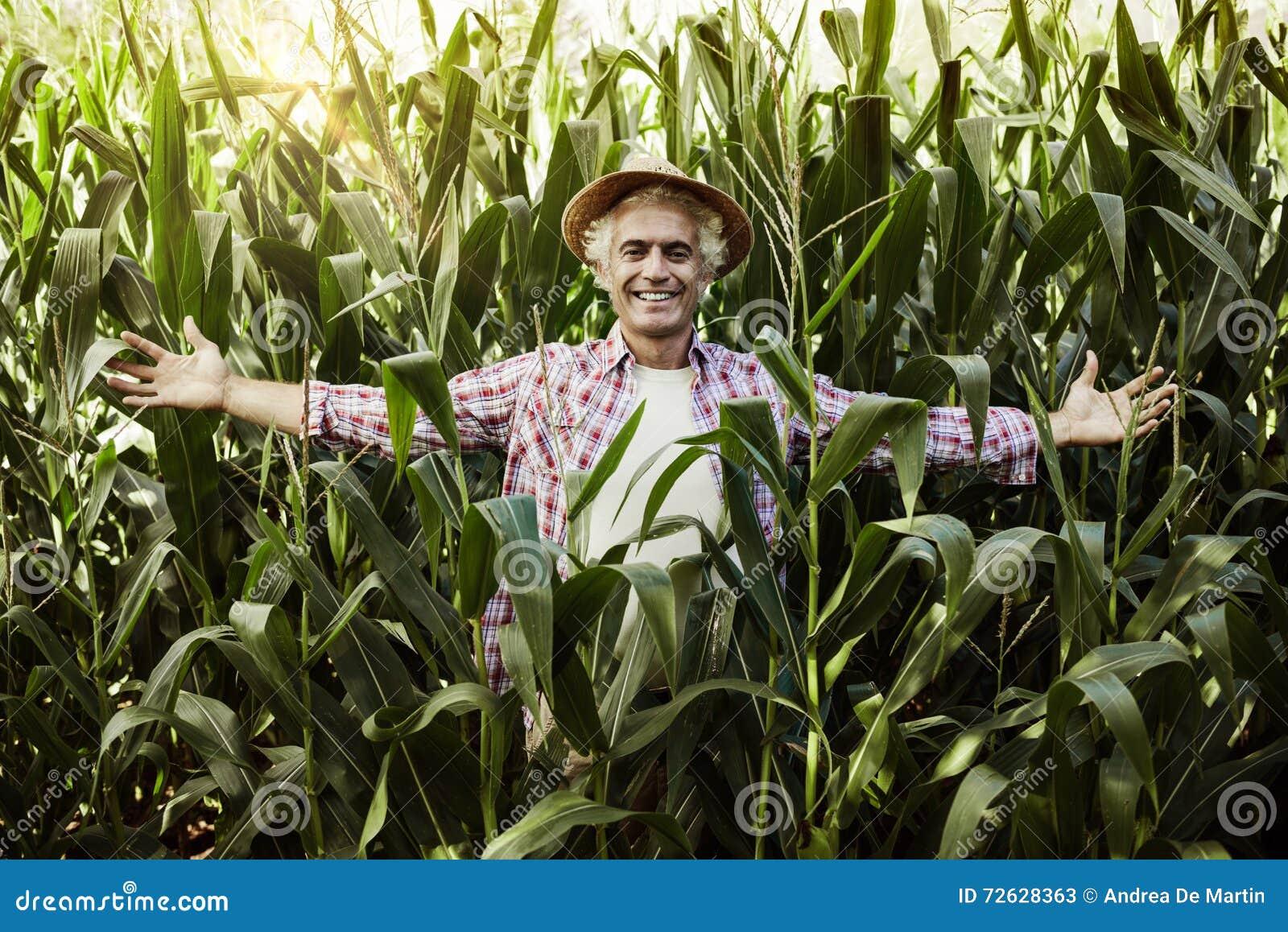 Glücklicher Landwirt, der auf dem Gebiet aufwirft
