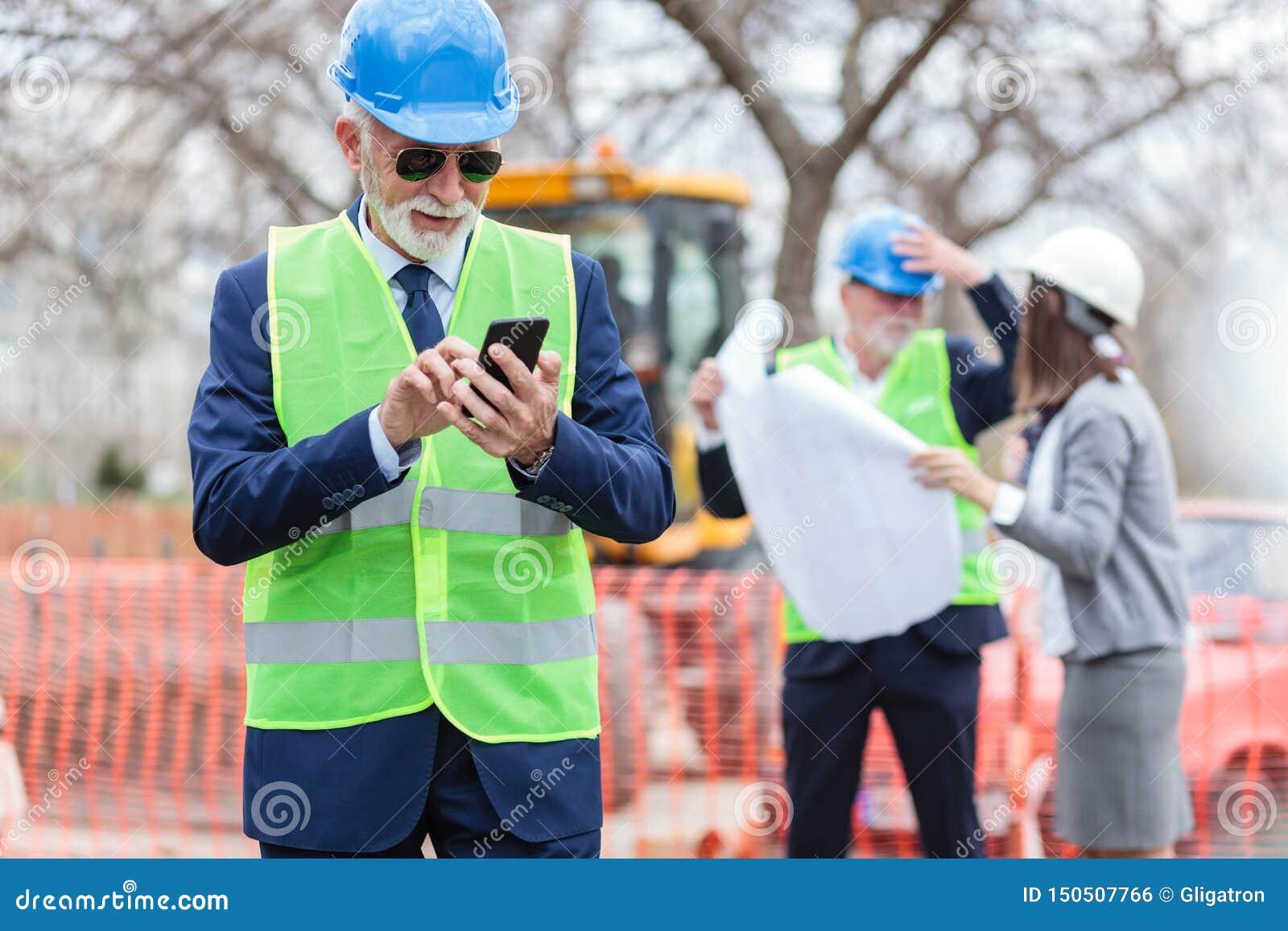Glücklicher leitender Ingenieur oder Geschäftsmann, der sein intelligentes Telefon bei der Untersuchung einer Baustelle verwendet