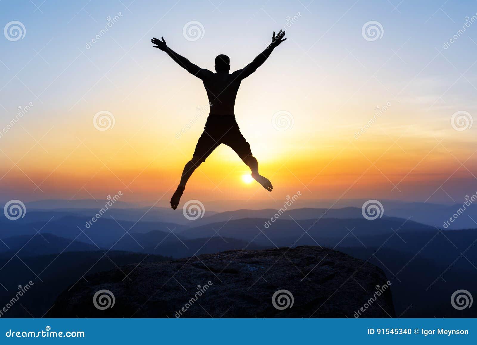 Glücklicher Mann, der für Freude auf der Spitze des Berges, Klippe bei Sonnenuntergang springt Erfolg, Sieger, Glück