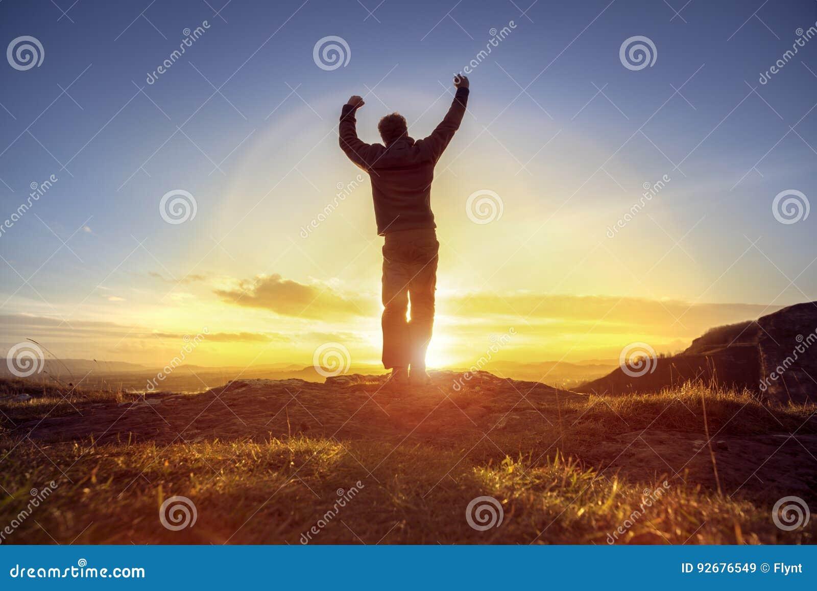 Glücklicher Mann, der gewinnenden Erfolg gegen Sonnenuntergang feiert