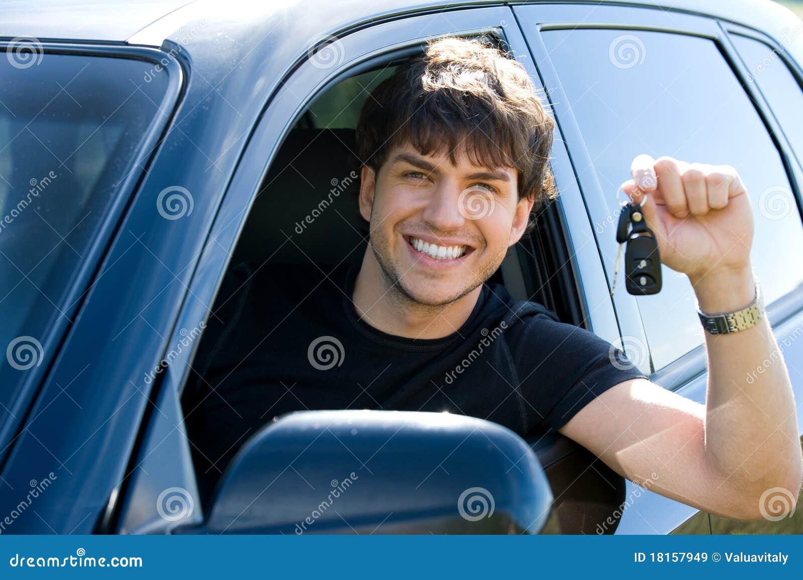 Glücklicher Mann, der Tasten im Auto zeigt