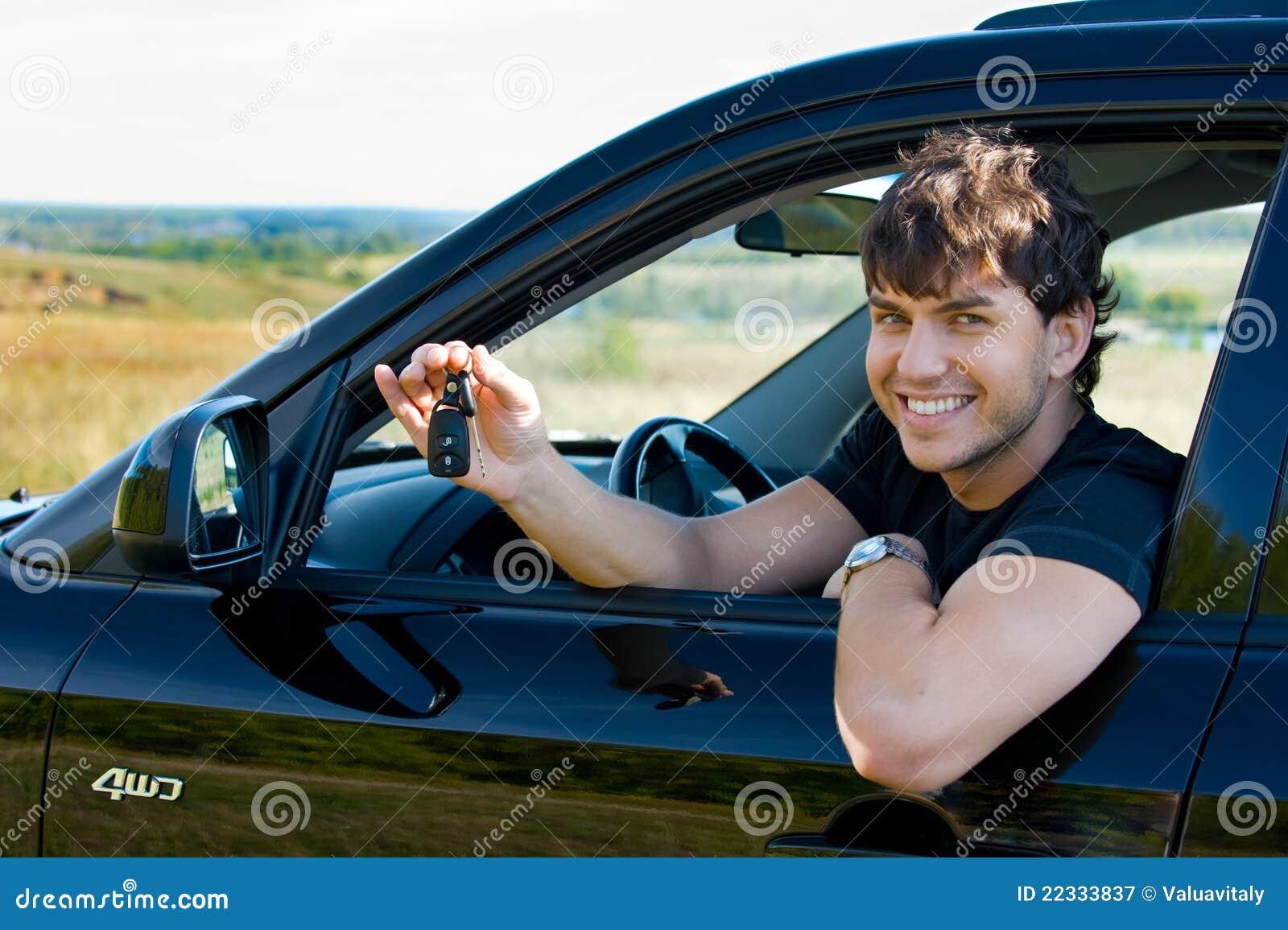 Glücklicher Mann, der Tasten vom Auto zeigt