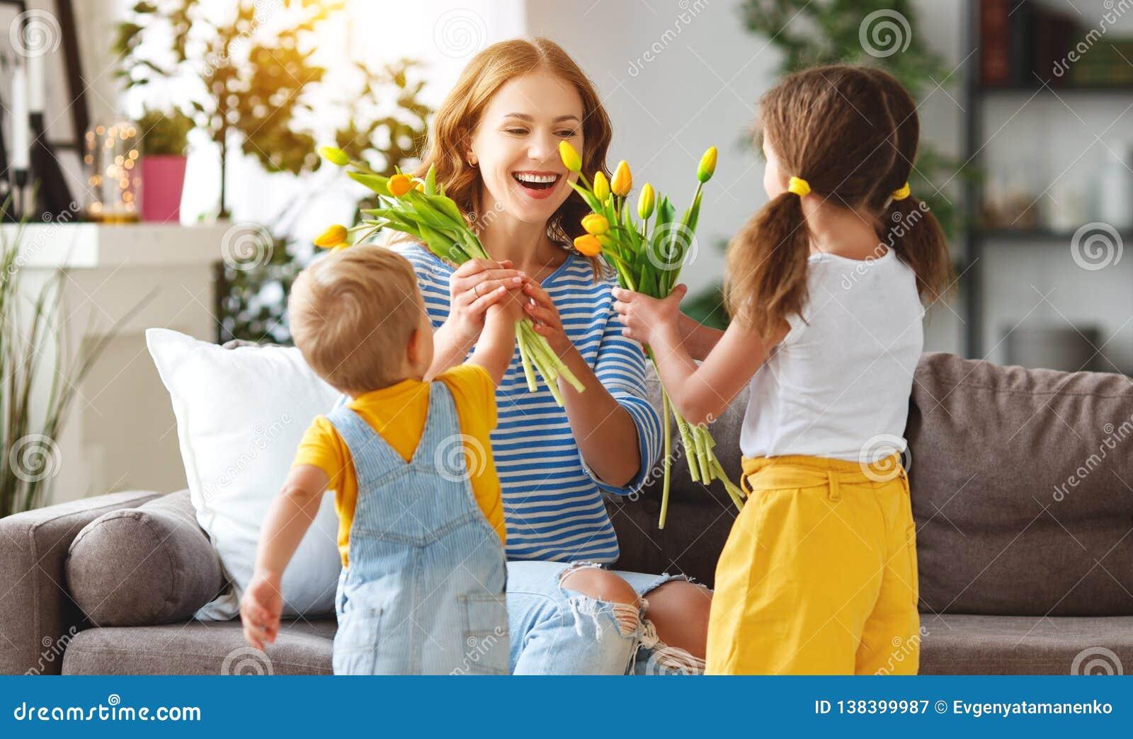 Glücklicher Muttertag! Kinder beglückwünscht Mütter und gibt ihr ein Geschenk und Blumen