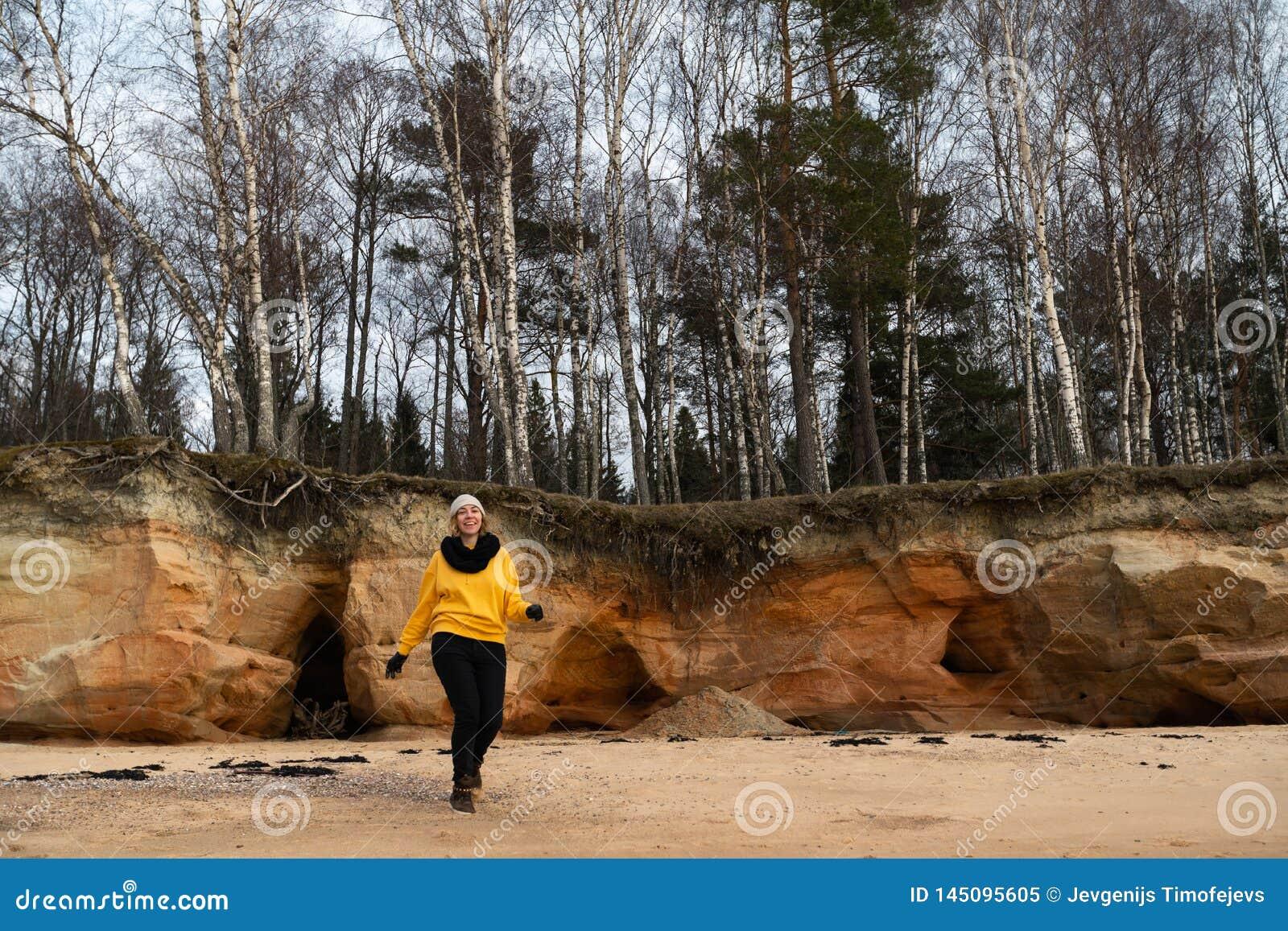 Glücklicher Sport- und Modeliebhaberenthusiast, der auf einem Strand trägt helle gelbe Strickjacke und schwarze Handschuhe und