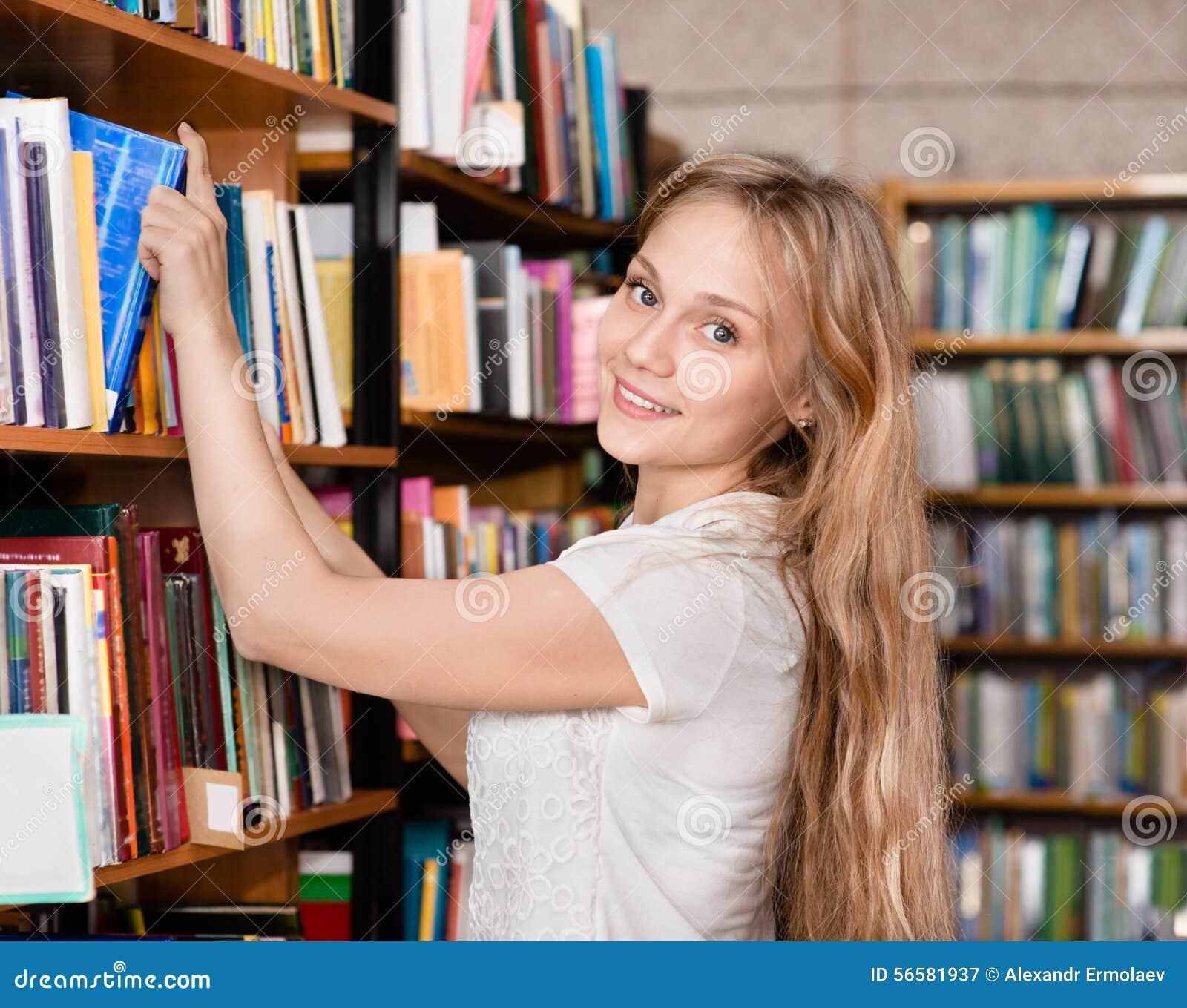 Glücklicher Student in der Bibliothek umgeben durch Bücher