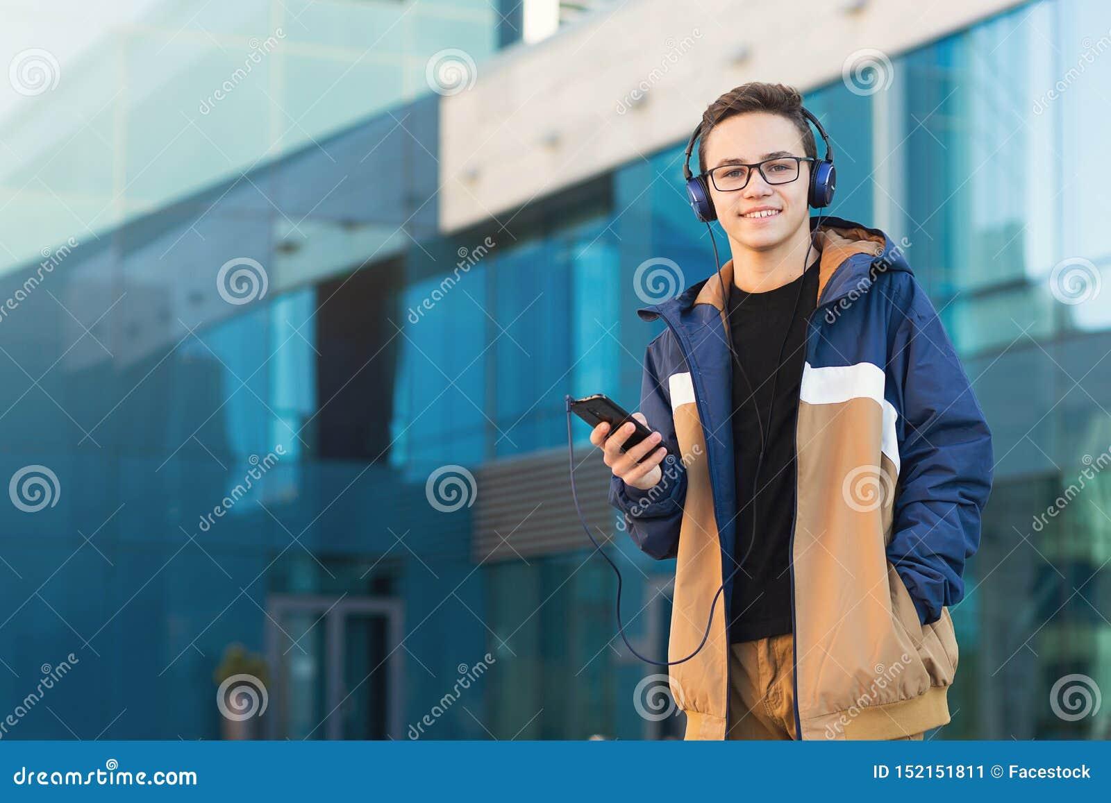 Glücklicher Student, der draußen Musik am Telefon hört Kopieren Sie Platz