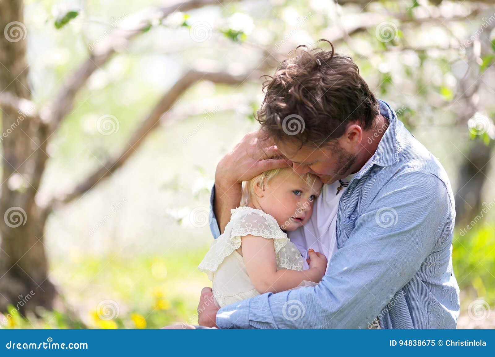 Glücklicher Vater Playing mit netter Babytochter in Autumn Woods