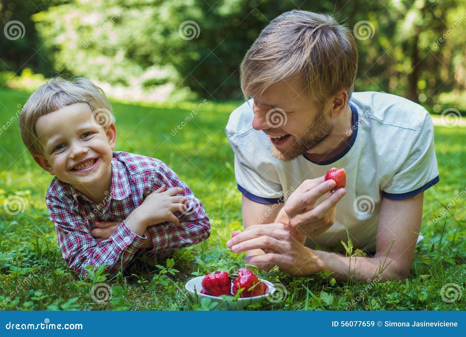 Glücklicher Vater und Sohn des Sommerfotos, die zusammen auf grünem Gras liegt