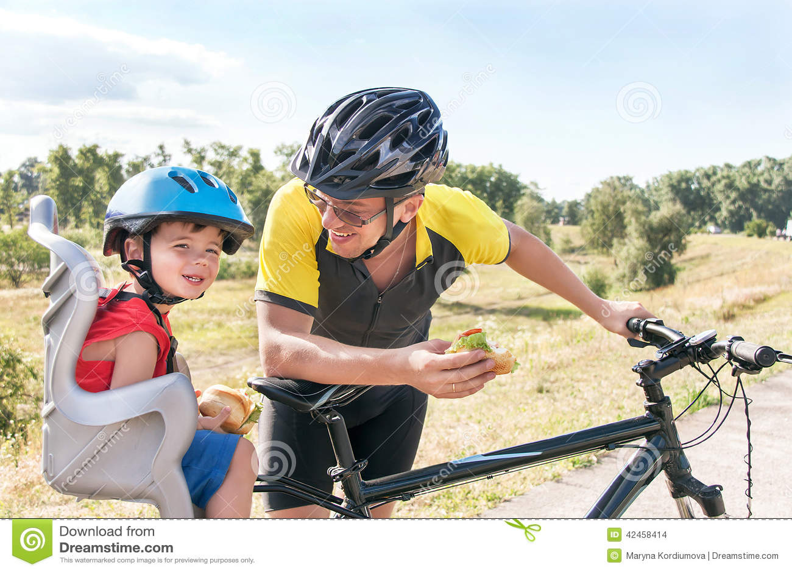Glücklicher Vater und Sohn isst das Mittagessen (Snack) während der Fahrradfahrt