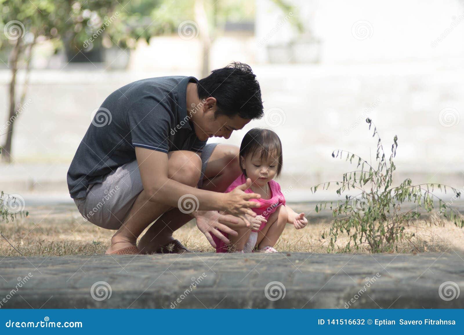 Glücklicher Vatertagelöhner und seine Tochter, die am Park mit wenigem Mädchen zeigt ihrem Vater etwas am sonnigen Tag spielt