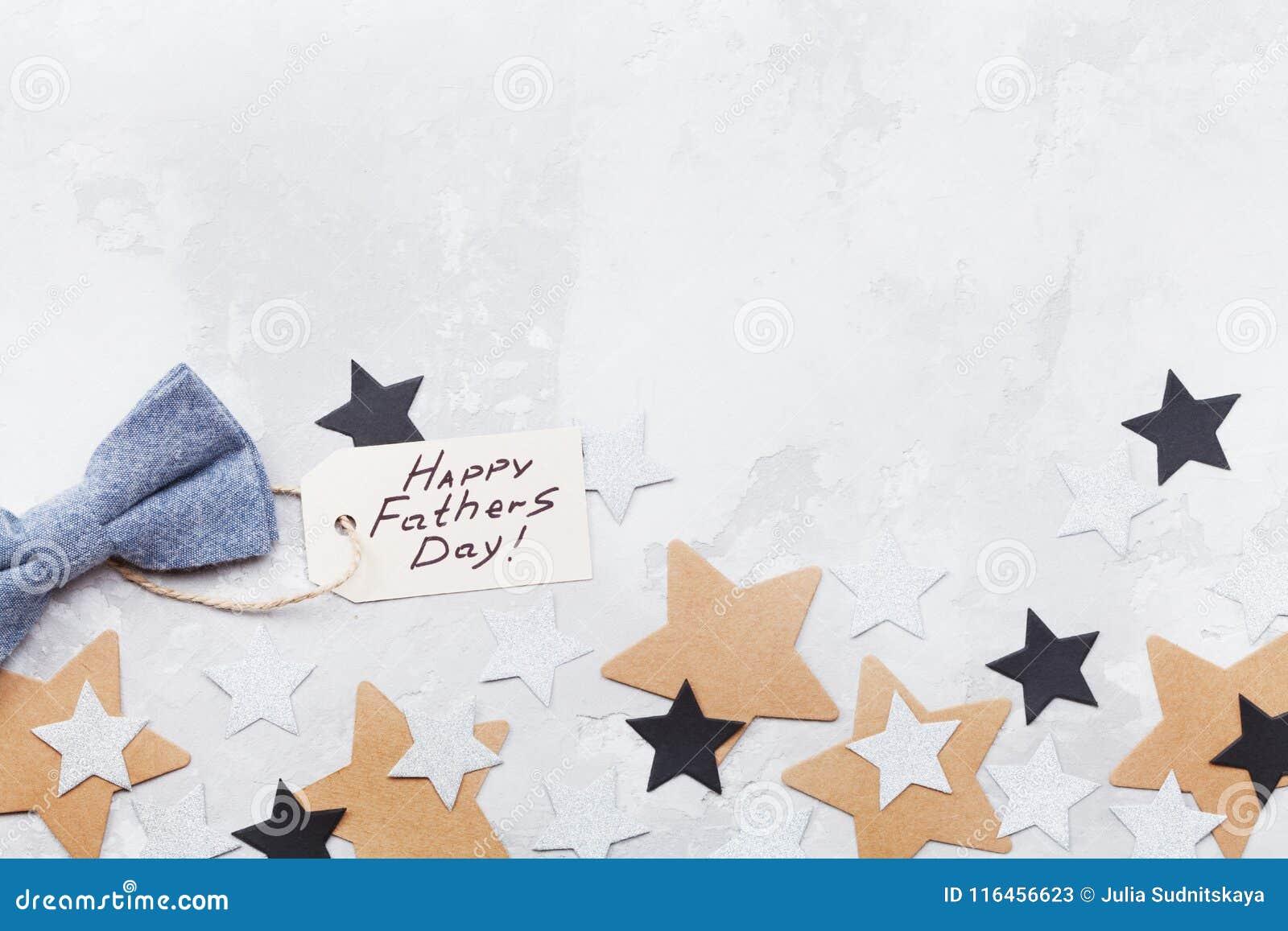 Glücklicher Vatertagshintergrund mit Grußtag, bowtie und Sternkonfettis auf Tischplatteansicht Flache Lagezusammensetzung