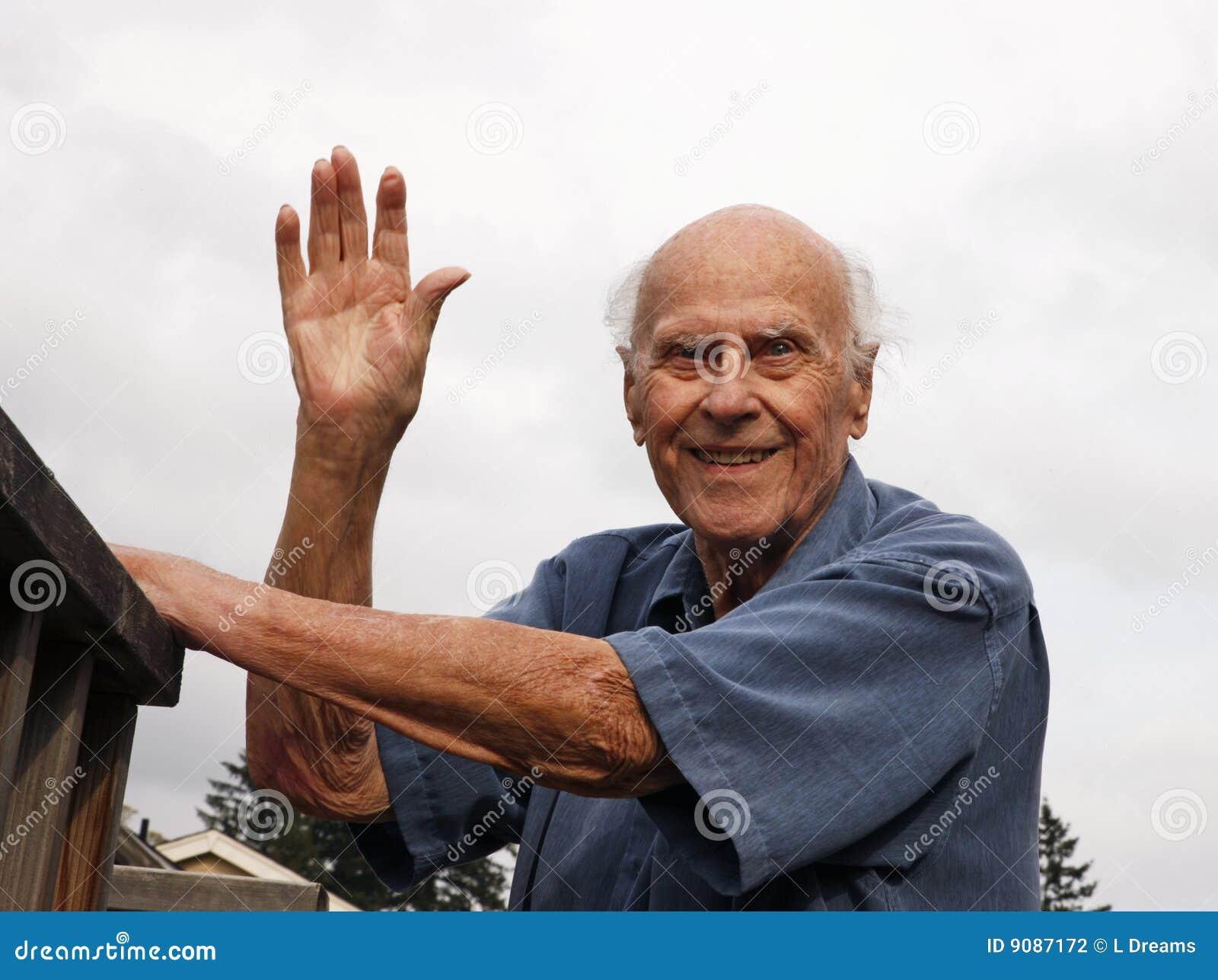 Glückliches älteres draußen wellenartig bewegen