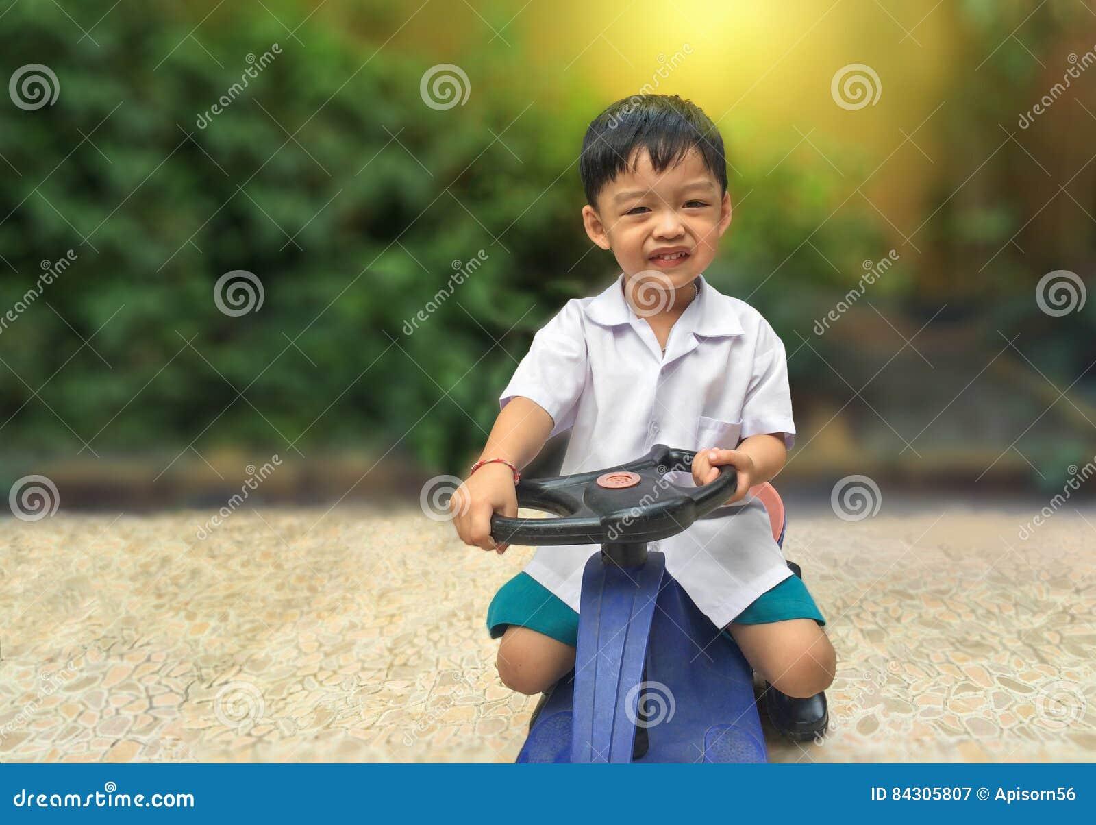 Glückliches Antriebsspielzeugauto des kleinen Jungen Spielerisches Kind am Spielplatz