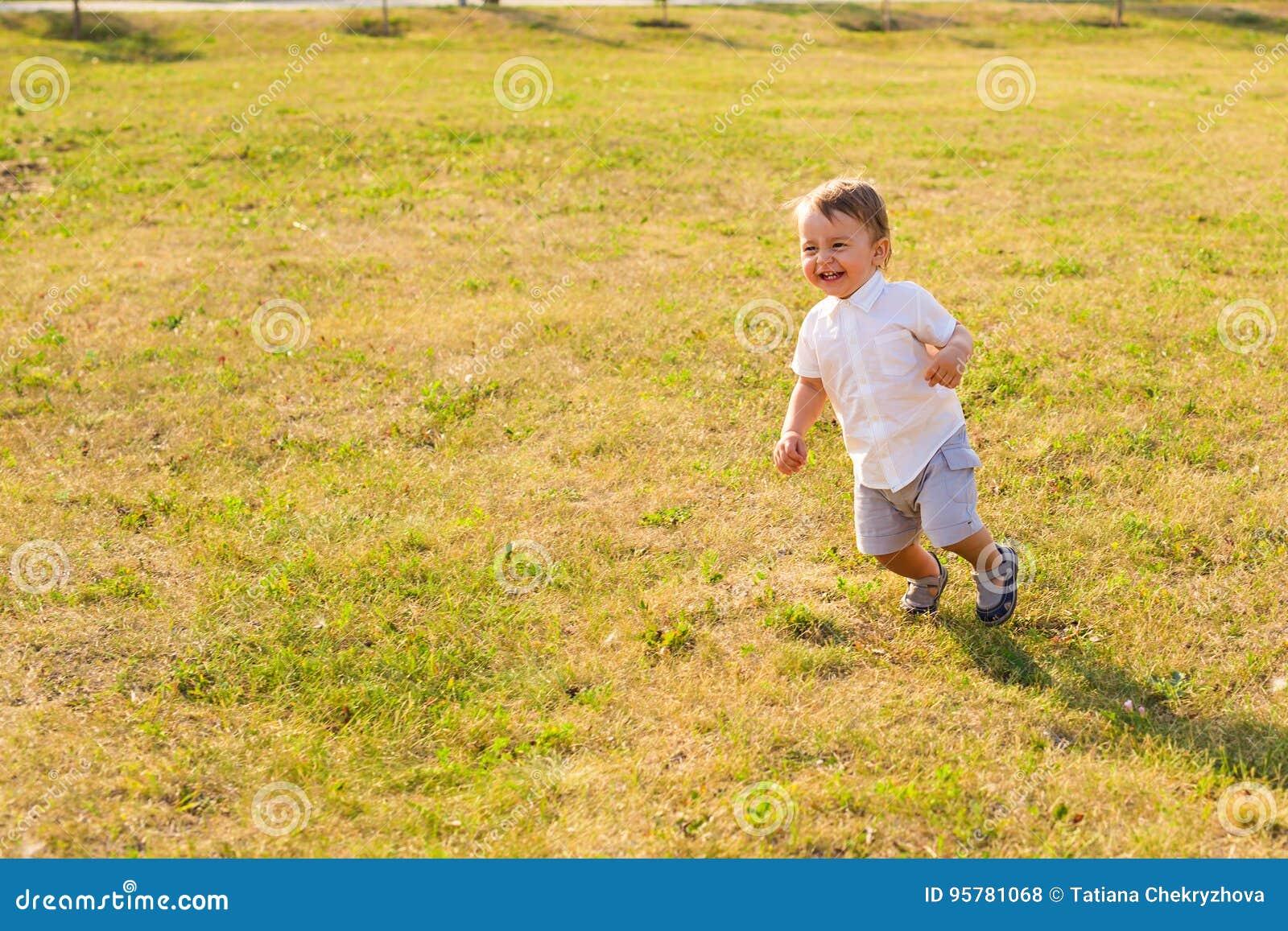 Glückliches Baby, das auf Sommerfeld läuft
