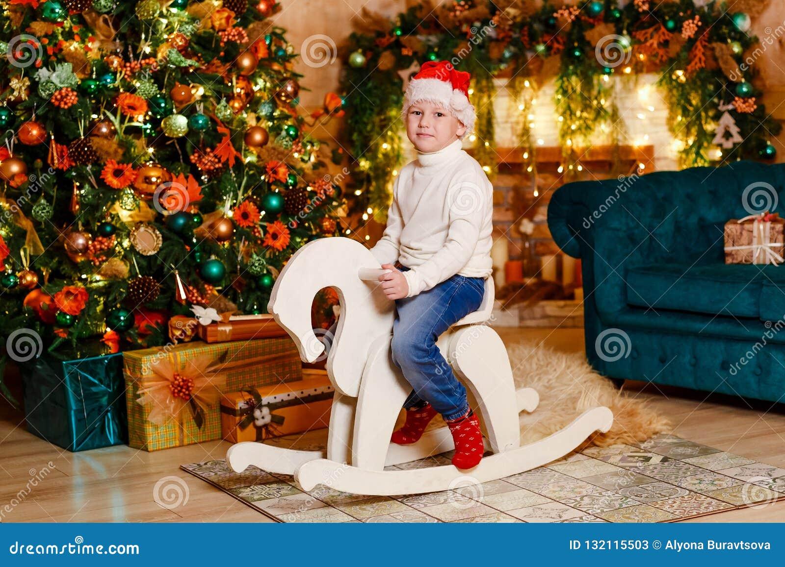 Glückliches Baby, das ein hölzernes Schaukelpferd des Spielzeugs in einem verzierten Weihnachtsraum reitet