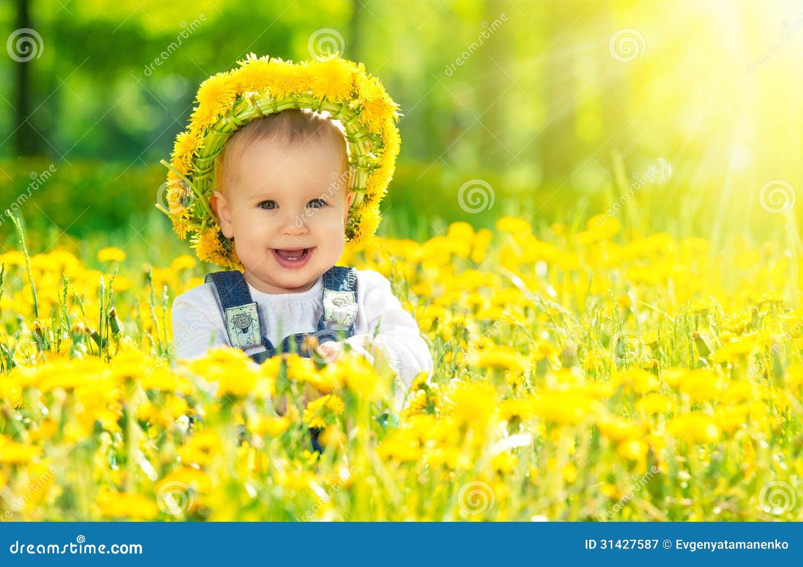 Glückliches Baby in einem Kranz auf Wiese mit gelben Blumen auf t