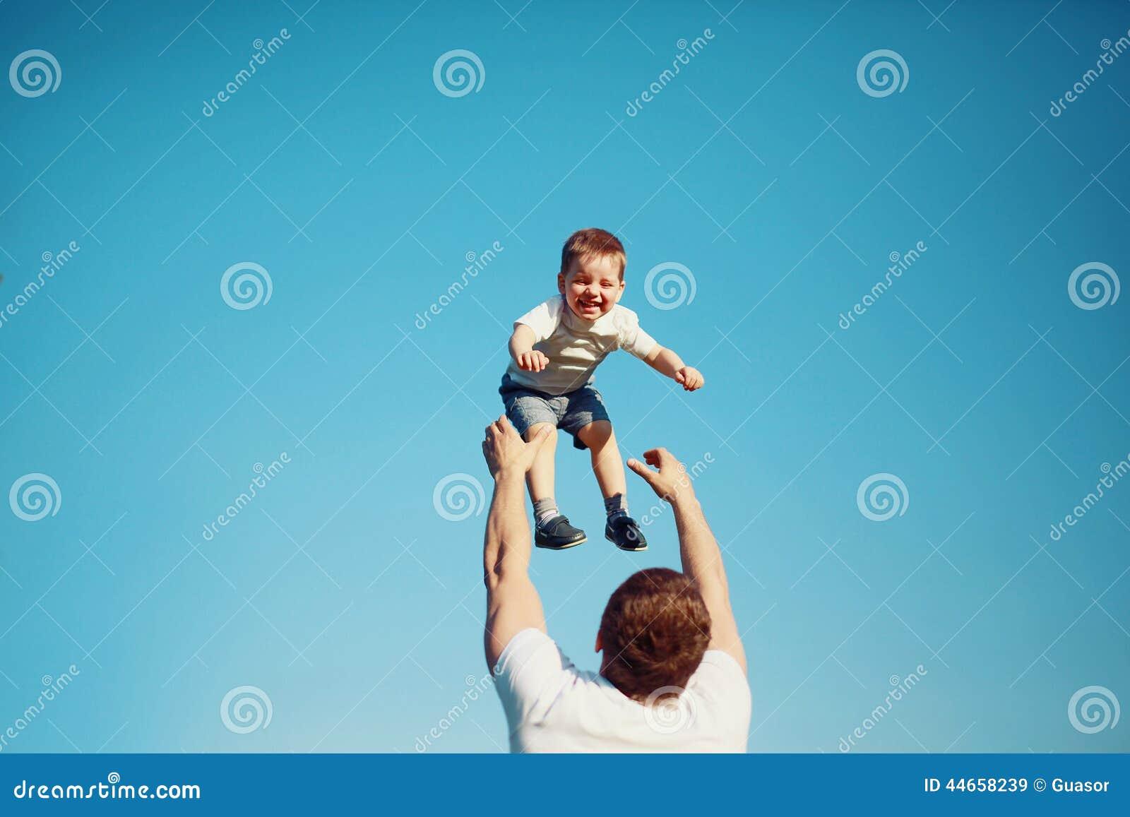 Glückliches frohes Kind, Vaterspaß wirft oben Sohn in der Luft, Sommer