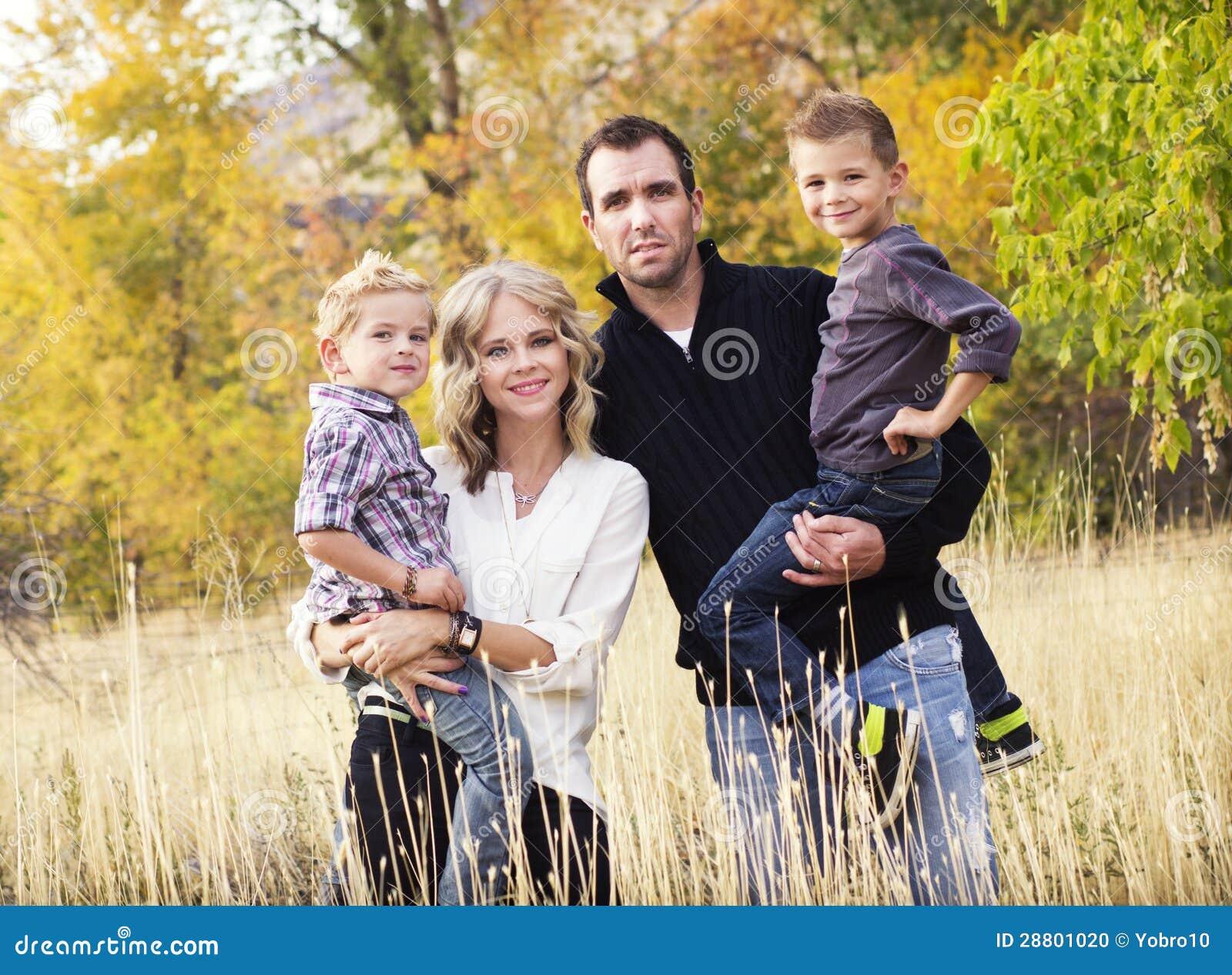 Glückliches junges Familien-Porträt mit Fallfarben