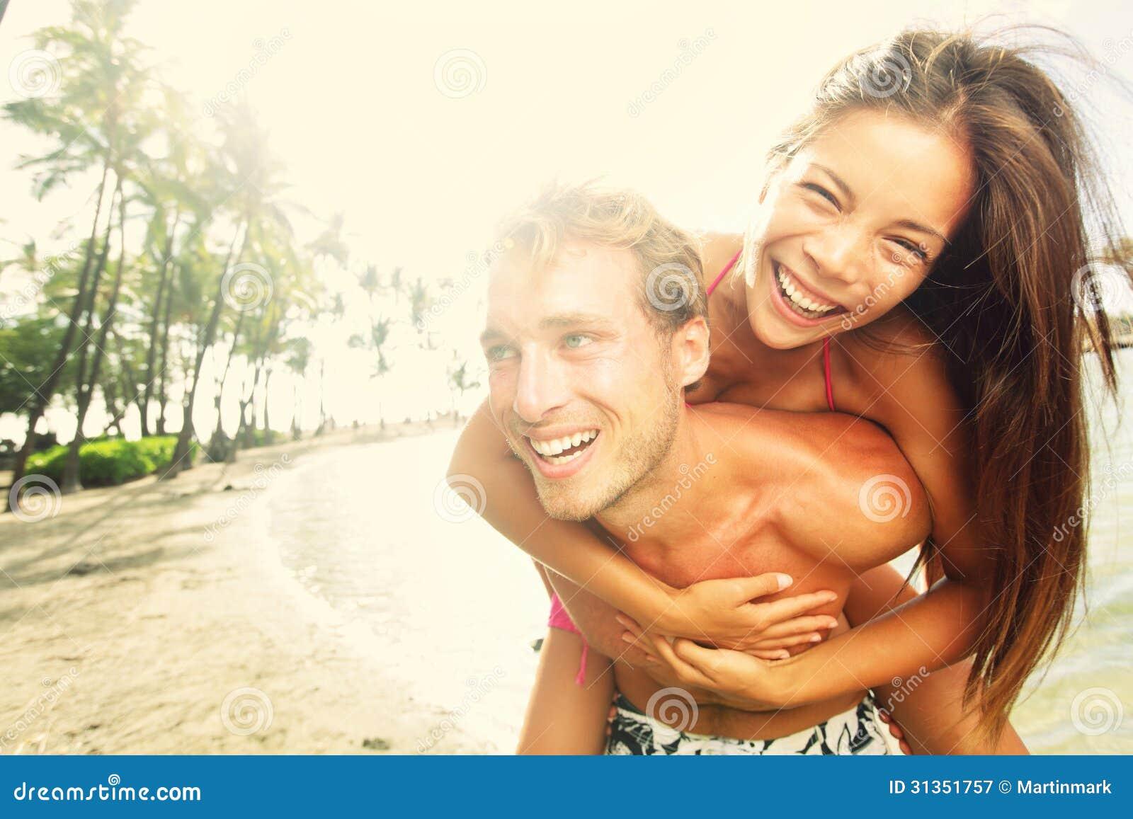 Glückliches junges frohes Paarstrand-Spaßlachen