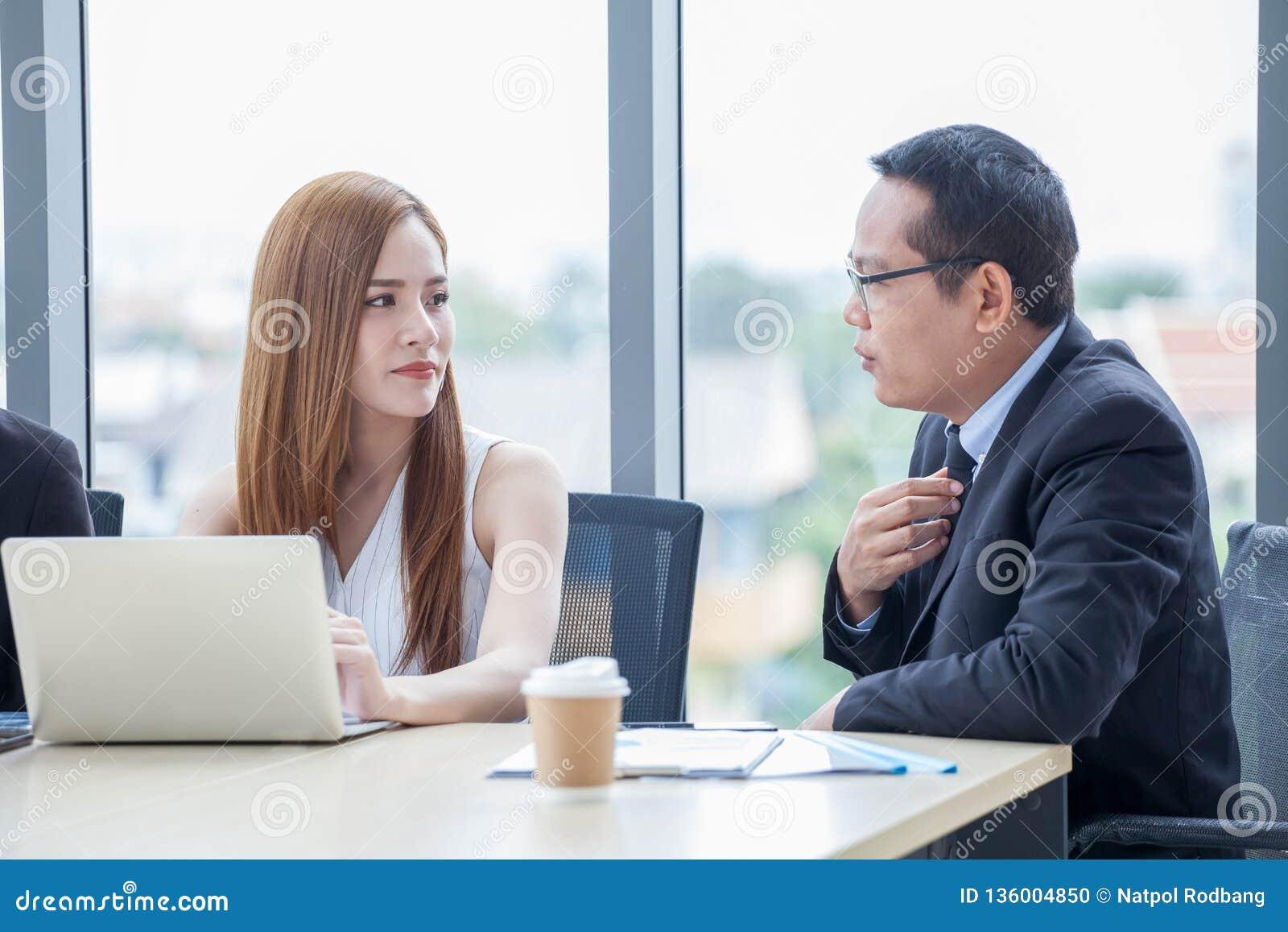Glückliches junges Geschäftsmann- und Geschäftsfrauteam, das zusammen mit Laptop-Computer auf dem Schreibtisch bespricht Informat