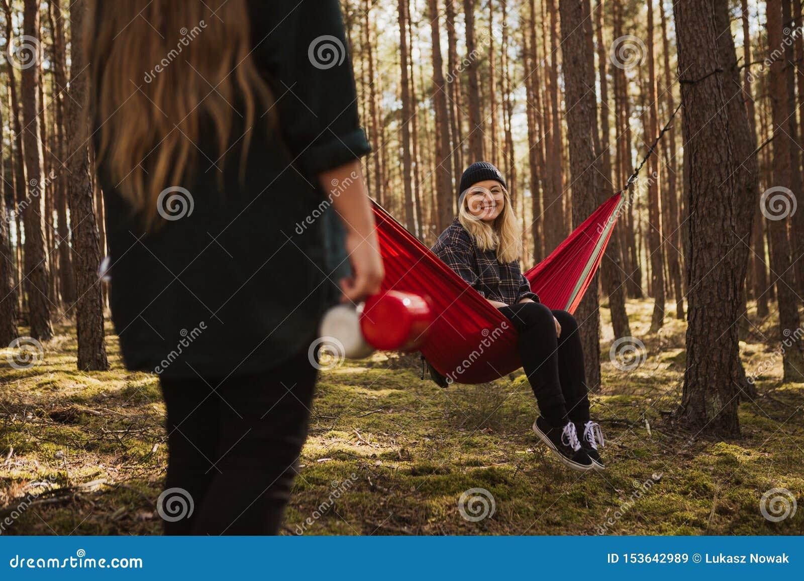 Glückliches junges Hippie-Mädchen genießt das Leben und Natur auf Hängematte mit anderer Frau im Sommerwald