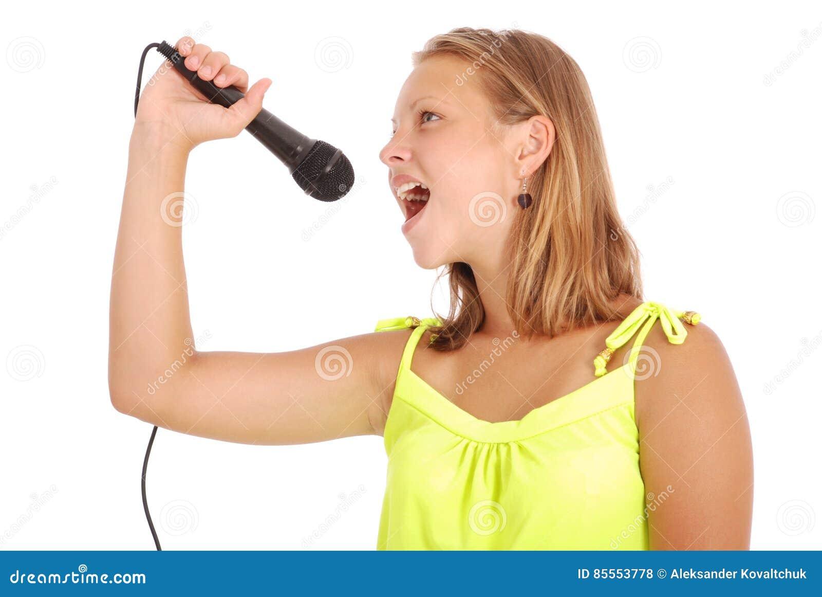 Glückliches junges schönes Mädchen, das mit Mikrofon singt