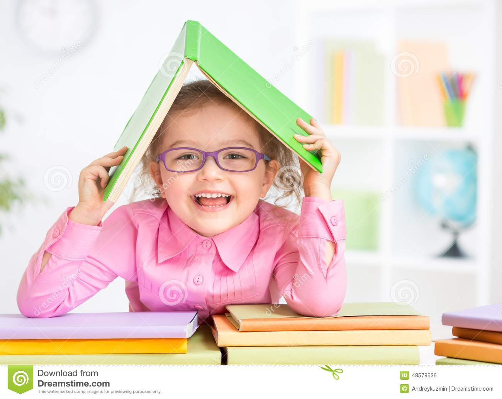 Glückliches Kind in den Gläsern unter dem Dach hergestellt vom Buch