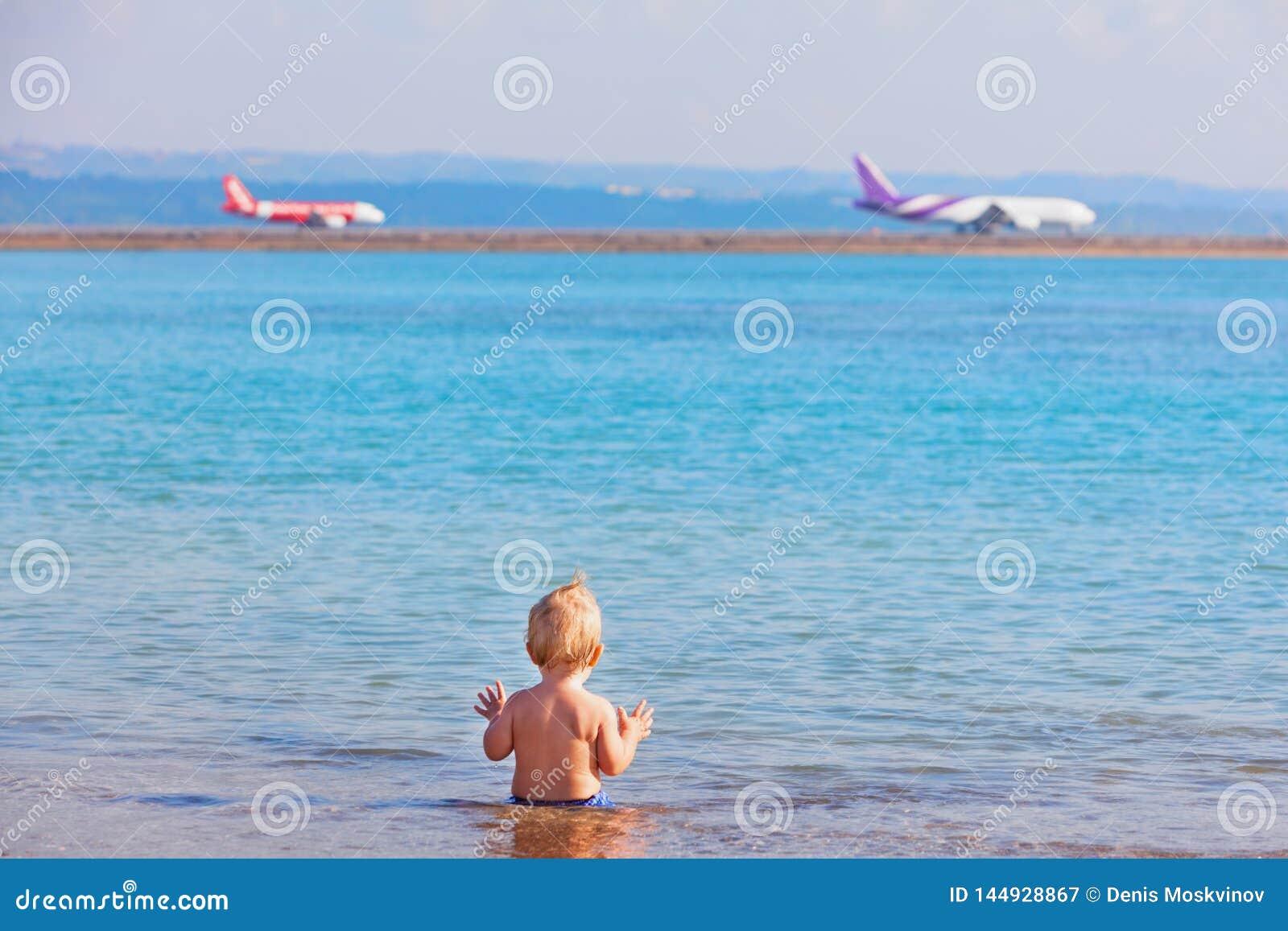 Glückliches Kinderaufpassende Flugzeuglandung am Strandflughafen