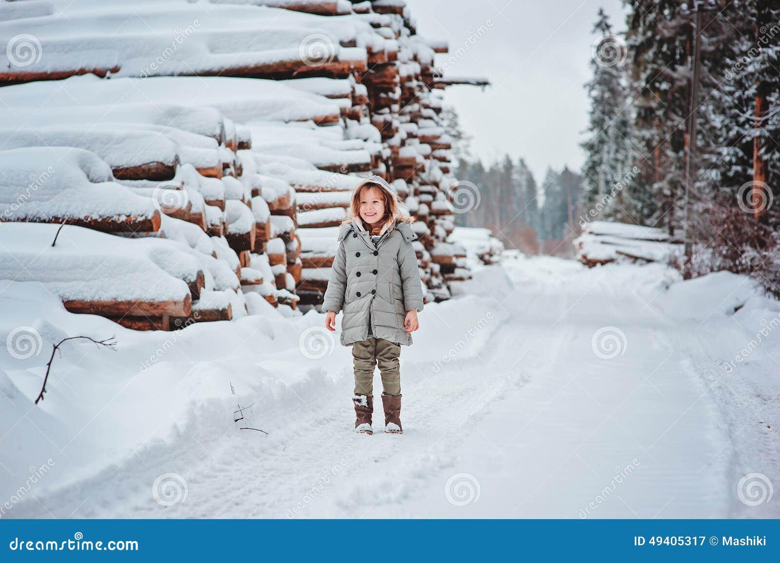 Download Glückliches Kindermädchen Auf Der Straße Im Schneebedeckten Wald Des Winters Mit Baumholzschlag Auf Hintergrund Stockbild - Bild von outdoor, portrait: 49405317