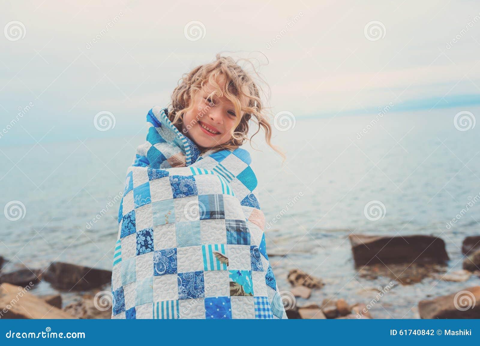 Glückliches Kindermädchen bedeckt in der Steppdeckendecke, gemütliche Sommerferien auf Küste