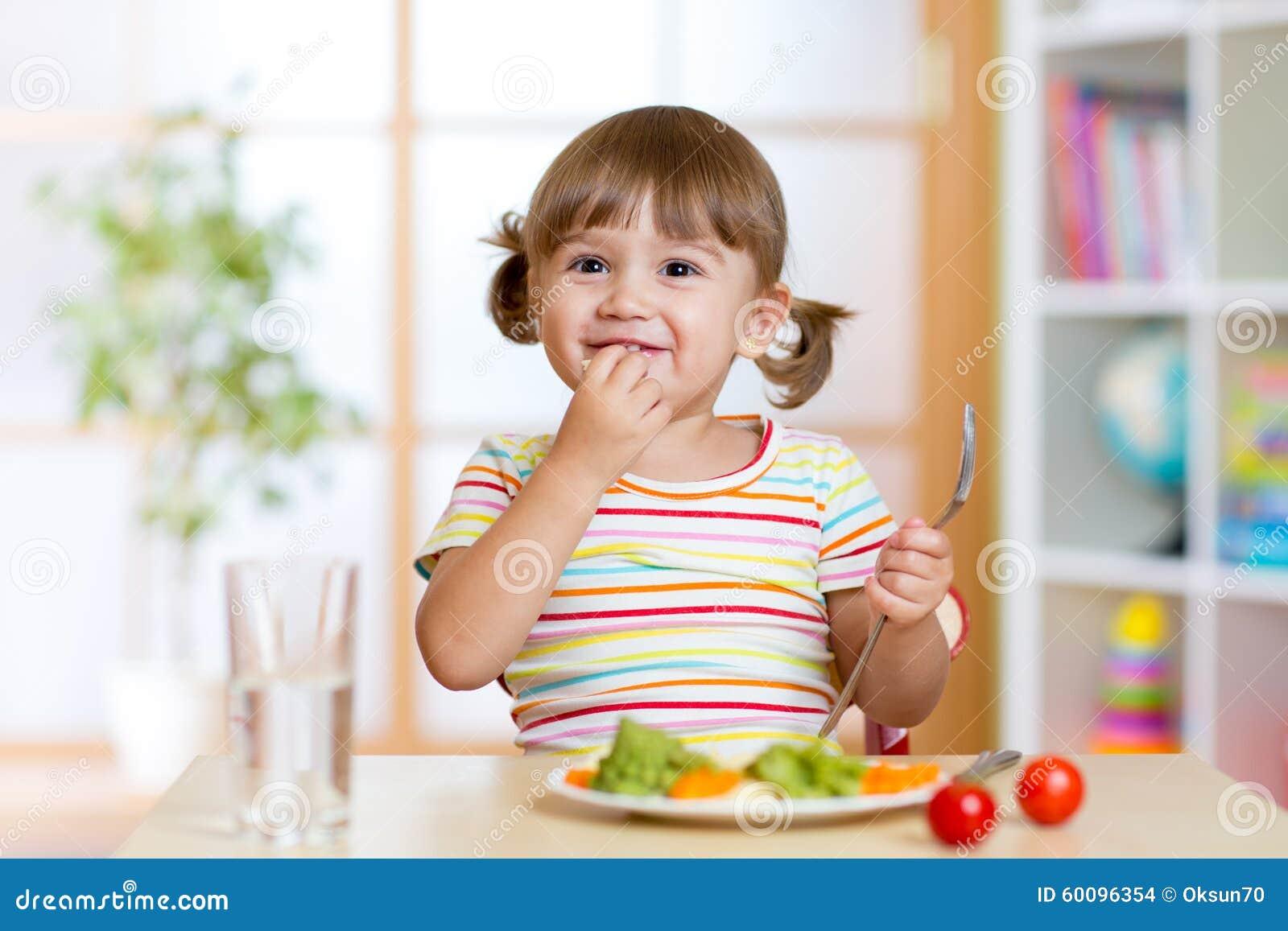 Glückliches Kindermädchen isst das Gemüse, das bei Tisch sitzt