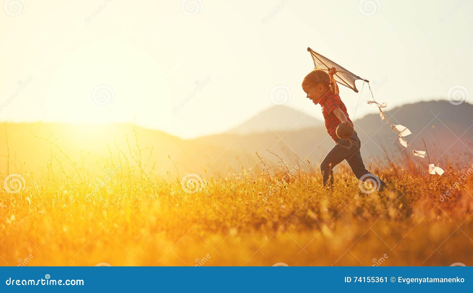 Glückliches Kindermädchen mit einem Drachen, der auf Wiese im Sommer läuft