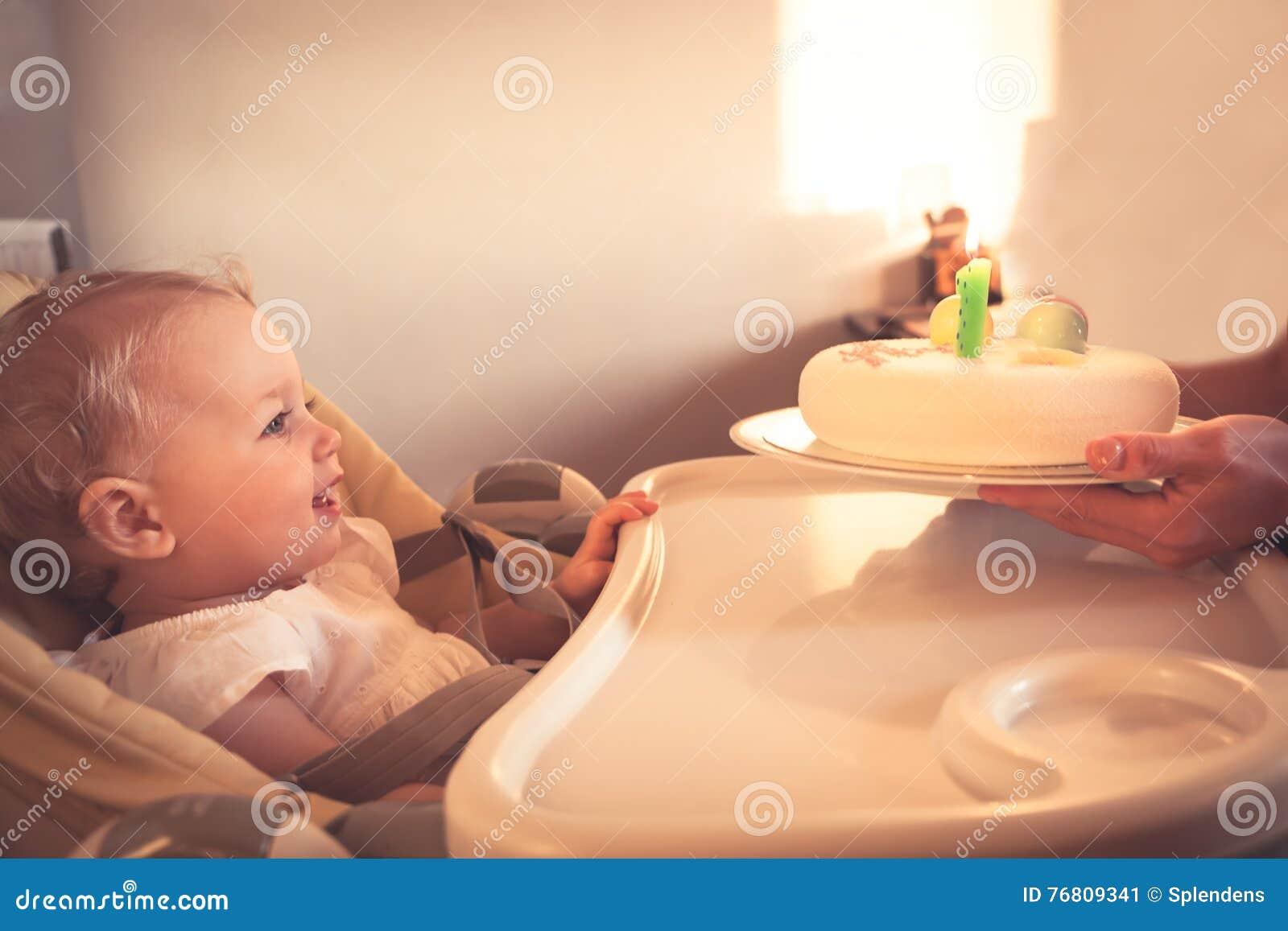 Glückliches kleines Kind, das Geburtstagskuchen mit brennender Kerze in seinem ersten alles Gute zum Geburtstag betrachtet