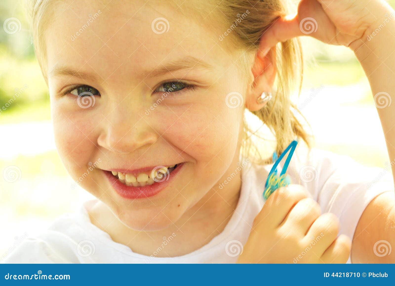 Glückliches kleines Mädchen, das Haarspange hält