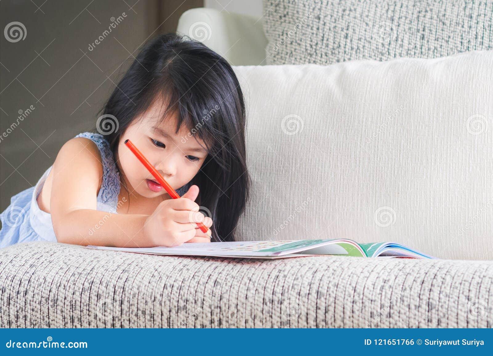 Glückliches kleines nettes Mädchen schreibt das Buch mit rotem Bleistift auf Th
