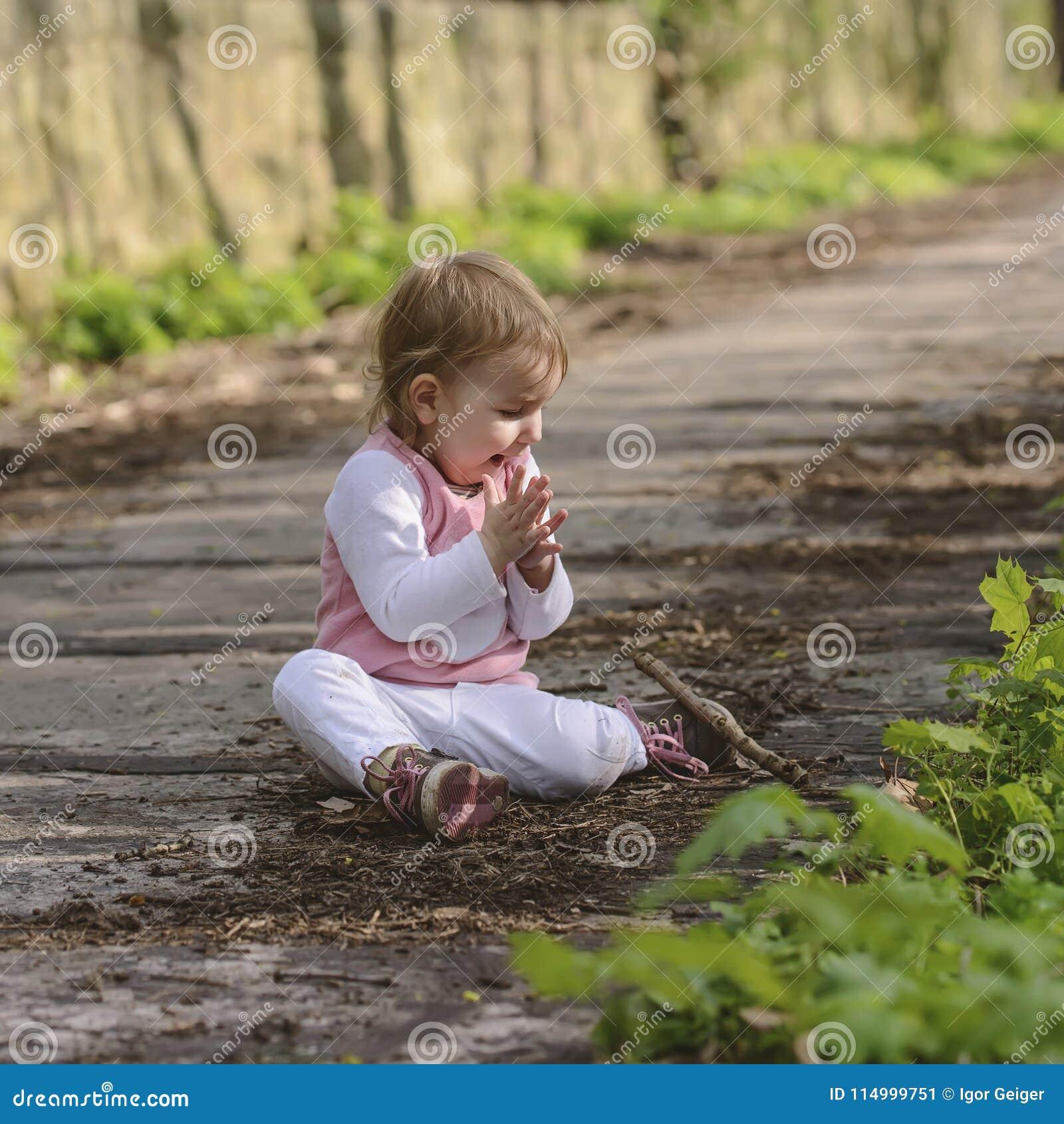 Glückliches kleines spielendes Baby beim Sitzen auf der Straße im Park