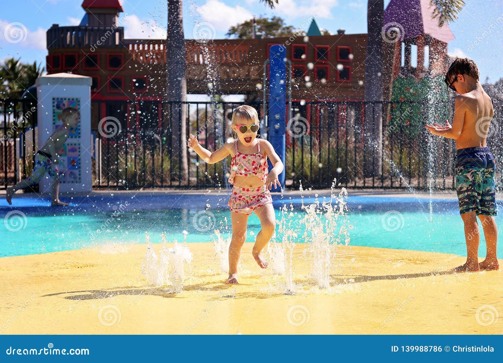 Glückliches Kleinkind-Kind, das in den Wasser-Brunnen am Spritzen-Park springt und spielt